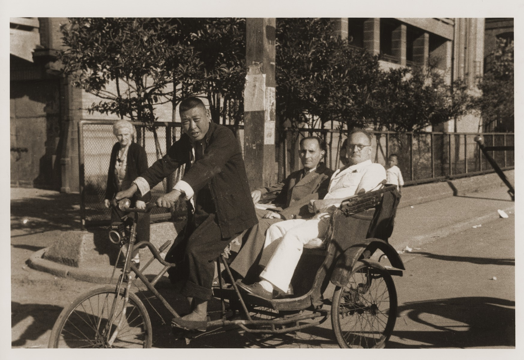 Two Jewish refugees ride in a pedicab.