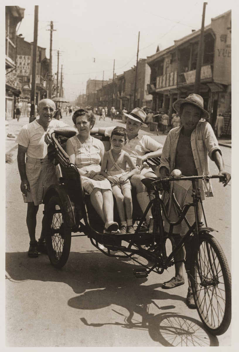 The Goldstaub family in front of their home on Tongshan Road.    Pictured from left to right are Adolf, Camilla and Eric Goldstaub.  Harry Fiedler sits between them in the pedicab.