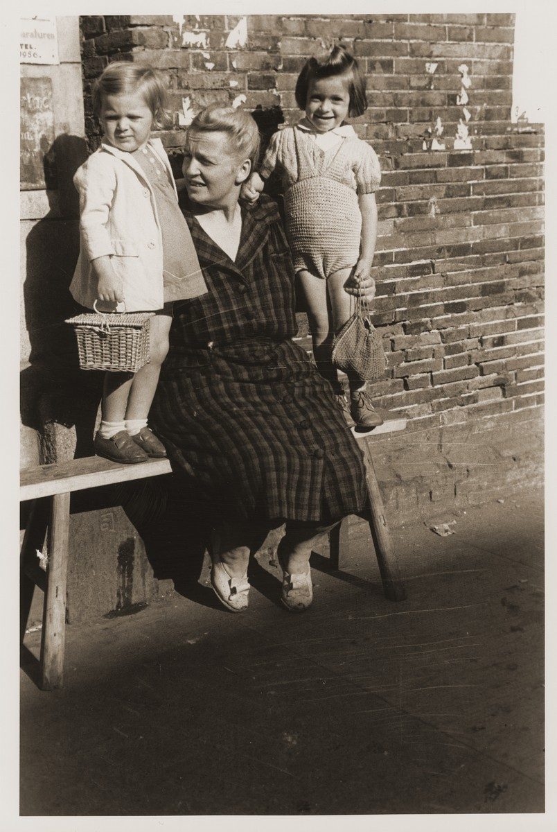 A Jewish refugee woman poses with two young children in Shanghai.