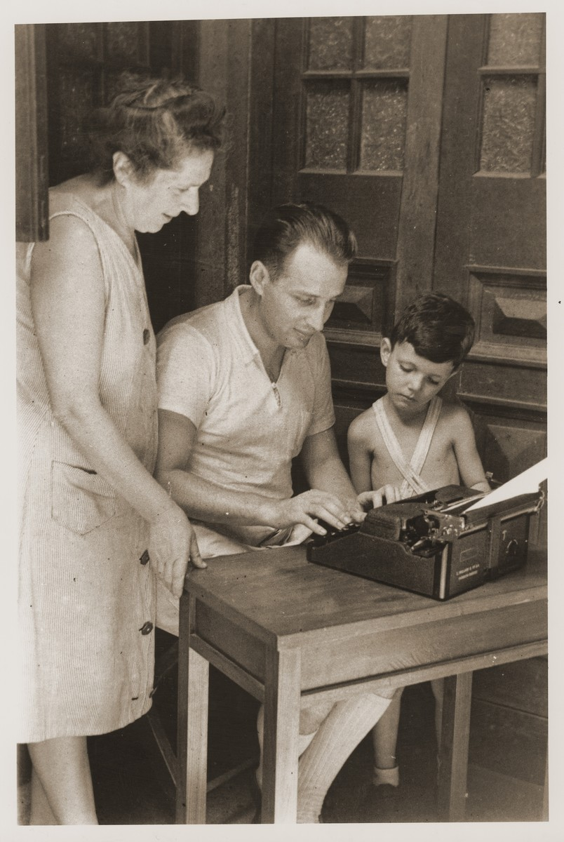 Eric Goldstaub types in his home on Tongshan Road as his mother, Camilla, and Harry Fiedler look on.