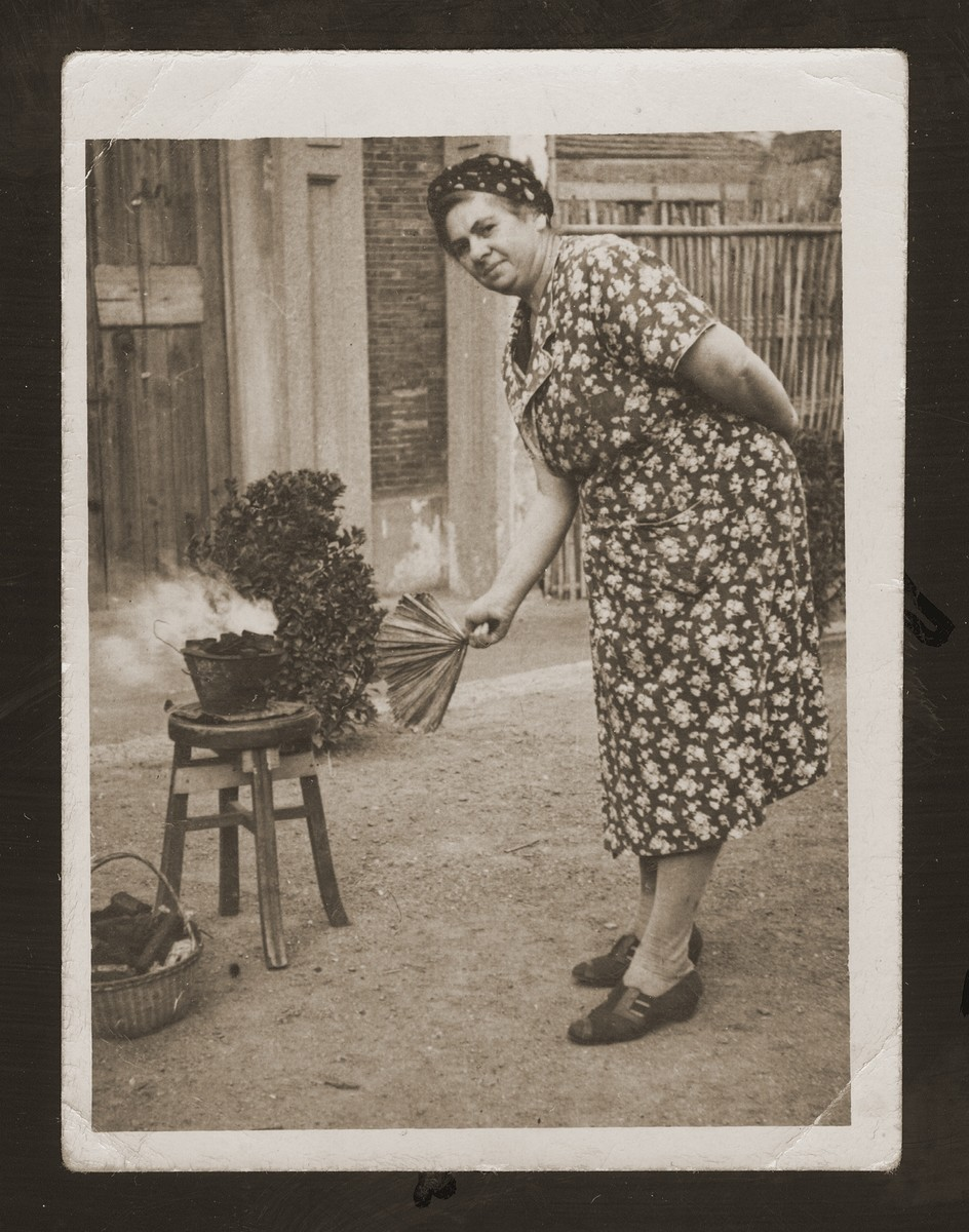 Else Blumenthal, the donor's aunt, fans a charcoal stove in front of her living quarters in Shanghai.  Such stoves were commonly used to reheat food obtained from a central kitchen.
