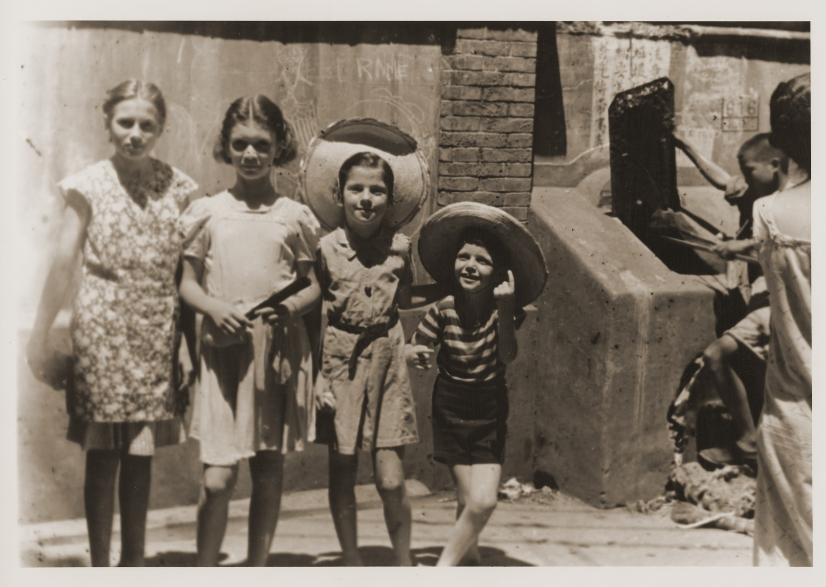 Jewish refugee children pose for a photograph on Tongshan Road.     Pictured from left to right are [unidentified girl], Olga (Irene) and Brigitte Gutstadt, and Harry Fiedler.  In the background, a child digs through garbage in search of food.