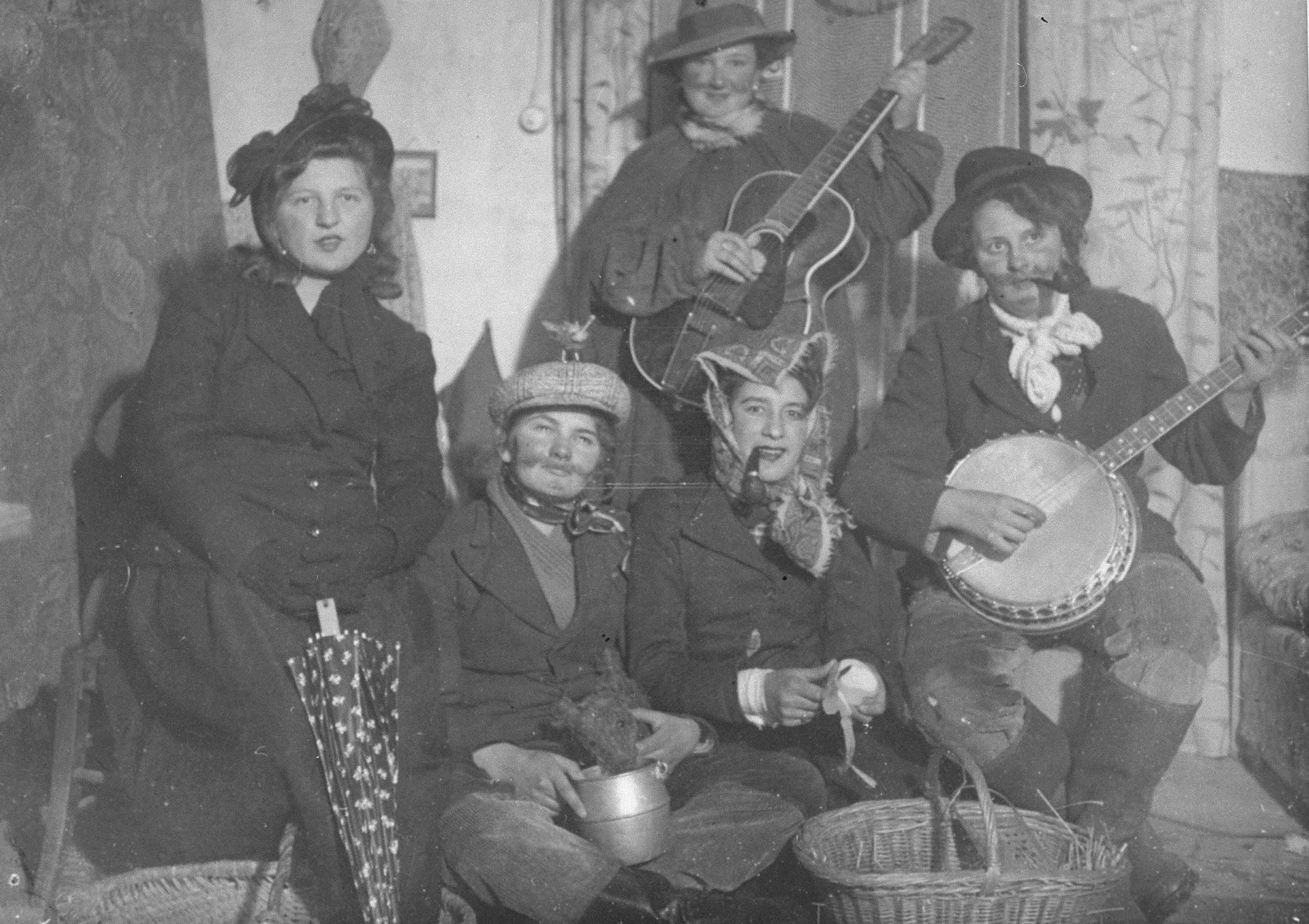 A Jewish teenager living in hiding in Saint Bonnet d'Orcival, France, takes part in a music/theater performance to raise money on behalf of local farmers who were prisoners of war.  Jacqueline Glicenstein, the Jewish teenager, is pictured standing in back with a guitar.  Jacqueline, together with her friend Bernadette, staged the entire performance.