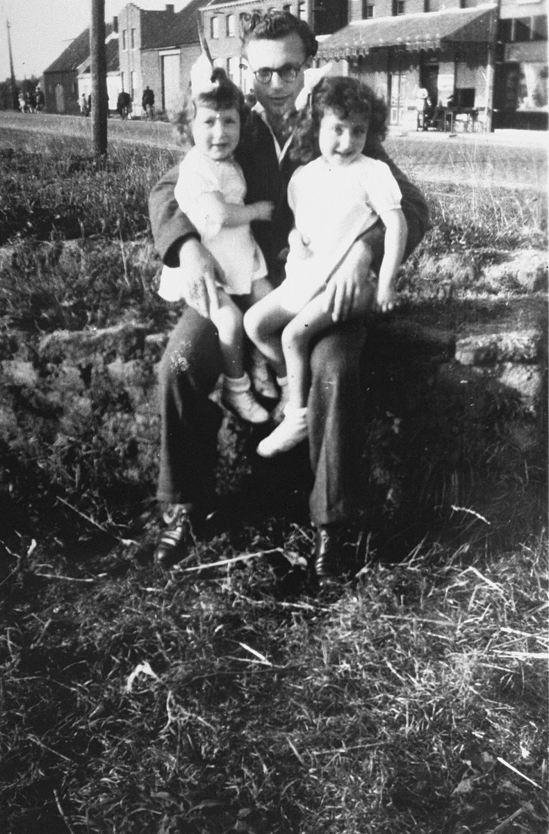 Margo and Annette Lederman, two Jewish children in hiding, sit on the lap of one of the van Buggenhout boys on the farm in Rumst, Belgium.