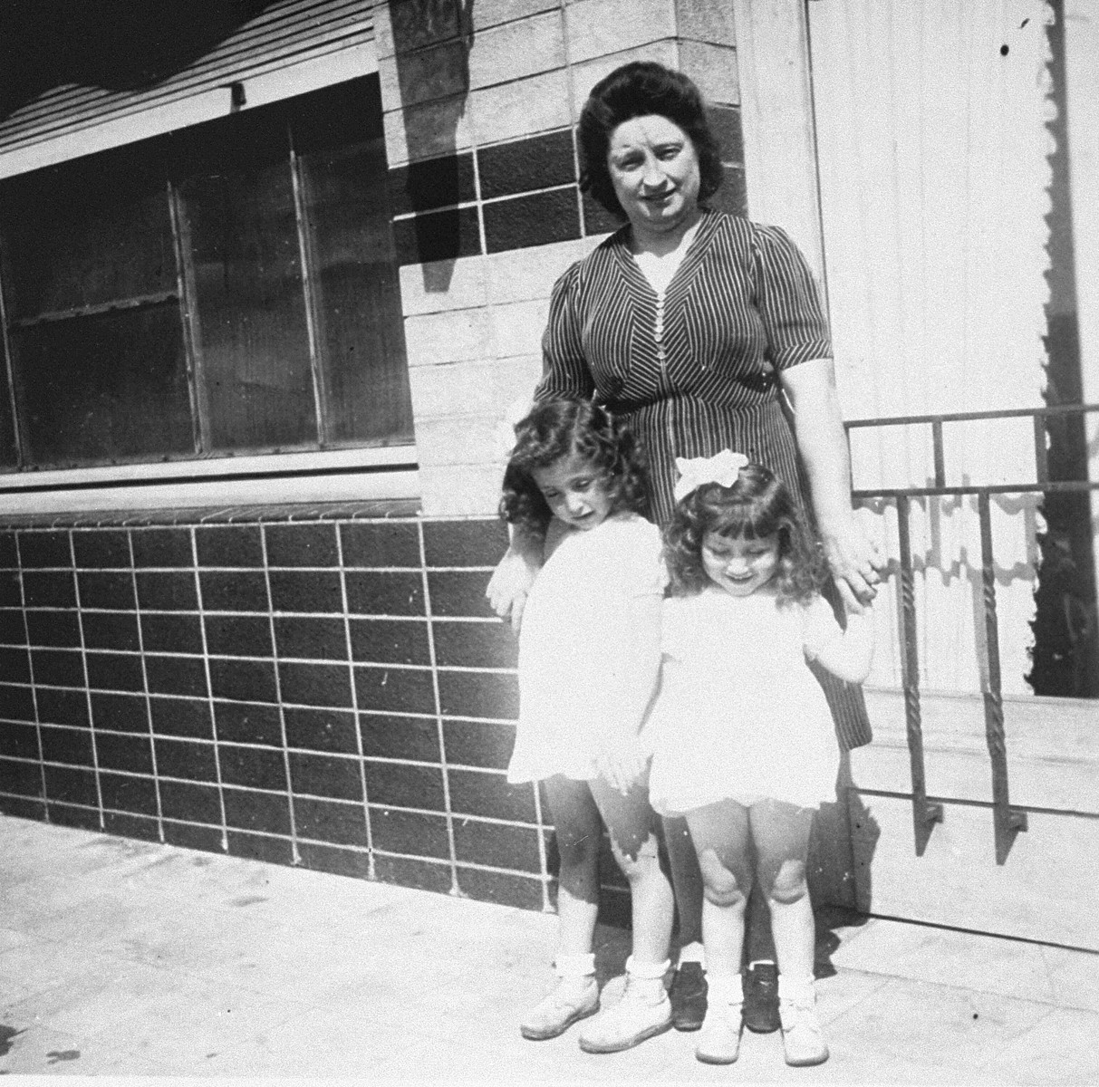 Annette and Margo Lederman, two Jewish children in hiding, pose with their rescuer, Clementine van Buggenhout, outside the cafe owned by the van Buggenhouts.