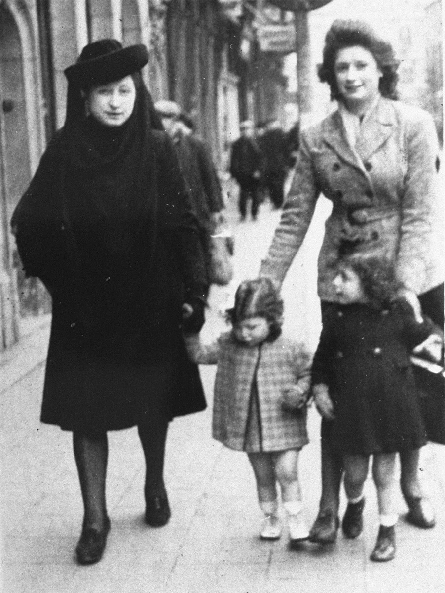 Margo and Annette Lederman, two Jewish children in hiding, walk along a street in Rumst, Belgium with their rescuers, Clementine and Lydia Buggenhout.
