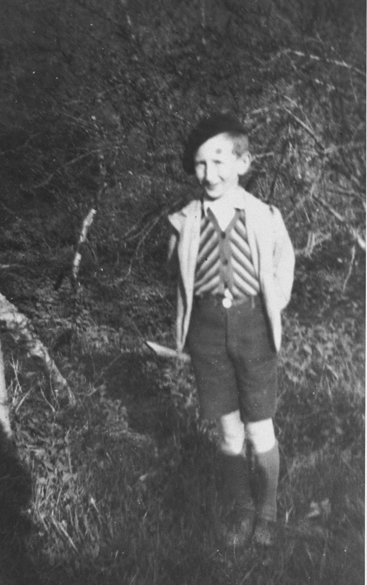 A Jewish boy who is living in hiding in Boissy-Saint-Leger, France, poses outside in front of  stone house.  Pictured is Michel Zilberstein.