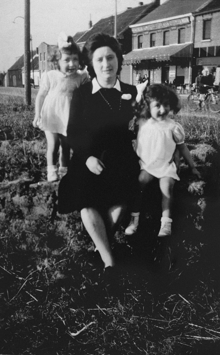 Margo and Annette Lederman, two Jewish children in hiding, pose with their rescuer, Clementine van Buggenhout near the van Buggenhout home.