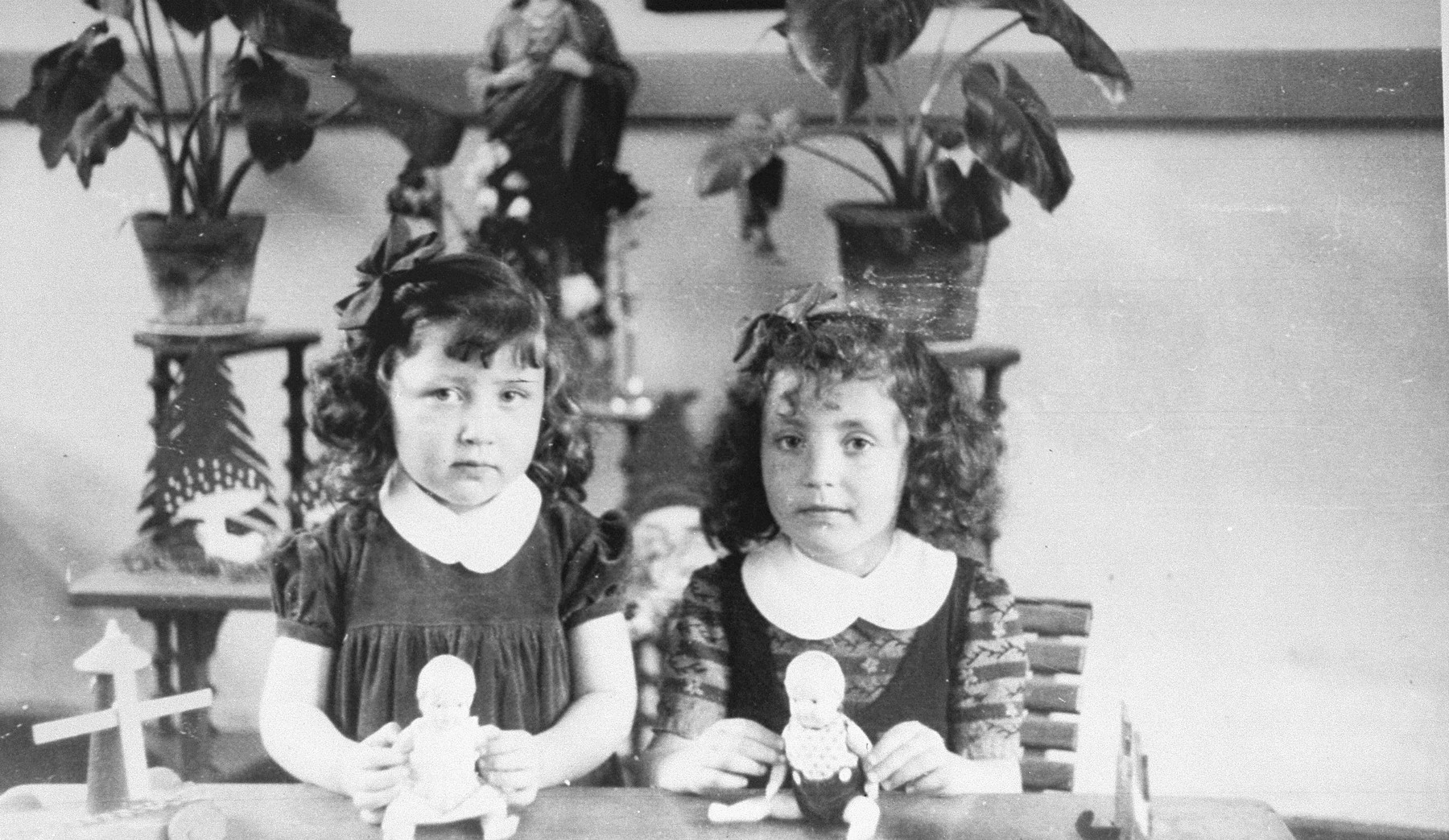 Margo and Annette Lederman pose with dolls given to them by their rescuers, Clementine and Edouard van Buggenhout.