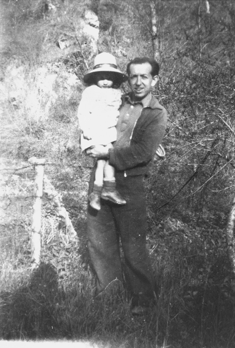 A Jewish father and daughter who are living in hiding in Boissy-Saint-Leger, France, pose outside near a fence.  Pictured are Georges and Olga Zilberstein.