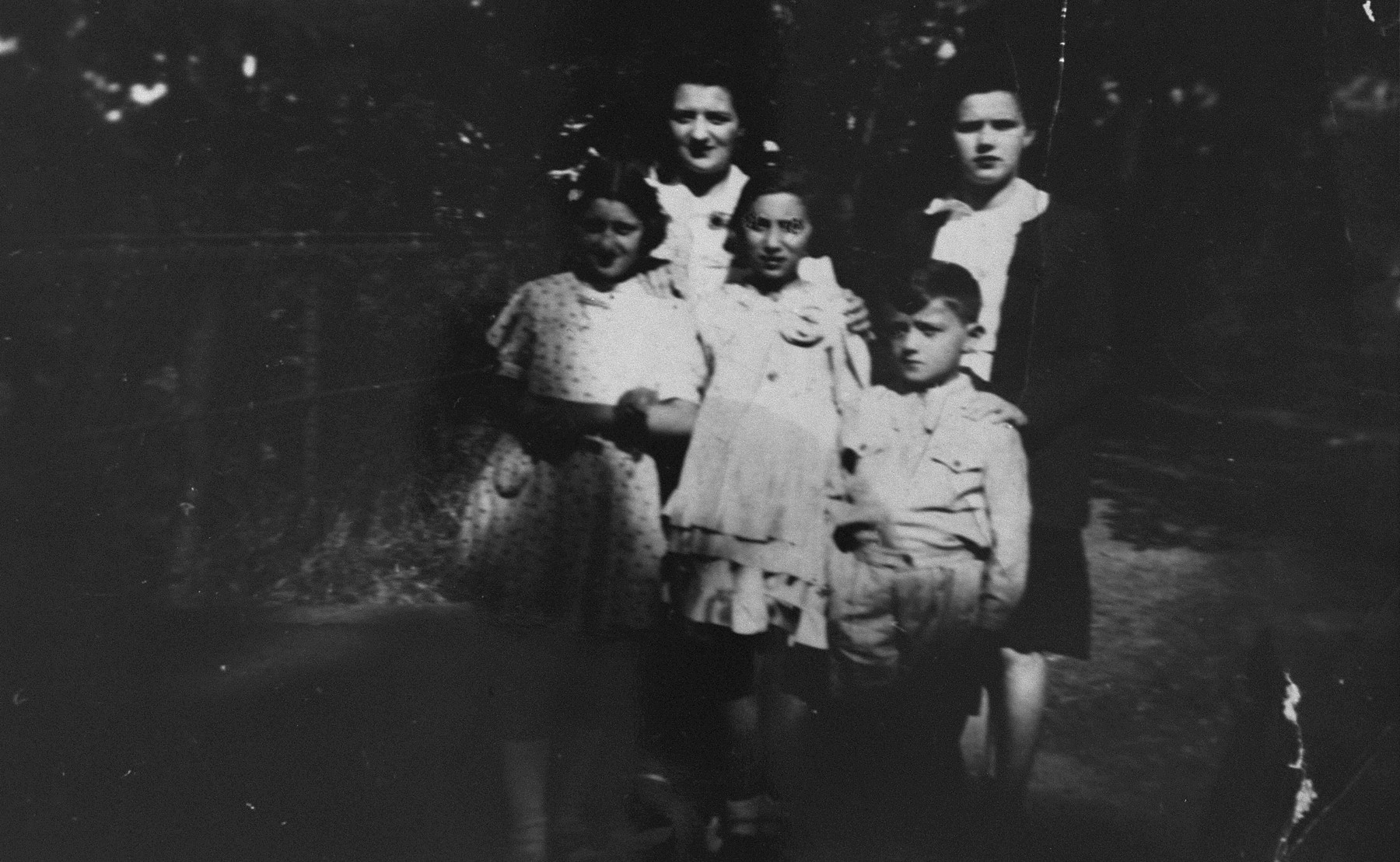 Chana Fajga Pesses poses with her children and members of the Leroux family, who are hiding them, during a visit to their home in Brou.  Pictured in the front row, from left to right, are: Berthe Pesses, Marcelle Rotleder, and Albert Pesses.  In the back row, from left to right, are: Chana Fajga Pesses and Edith Leroux.