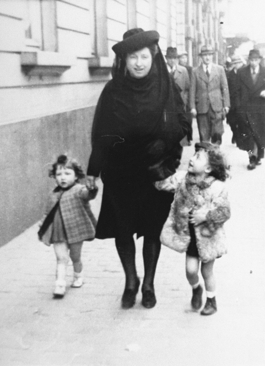 Margo and Annette Lederman, two Jewish children in hiding, walk along a street in Rumst, Belgium with their rescuer, Clementine van Buggenhout.