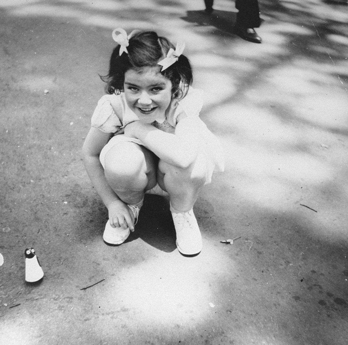 A young Jewish girl who is living in hiding in German-occupied France, plays outside with a toy.  Pictured is Josette Glicenstein.