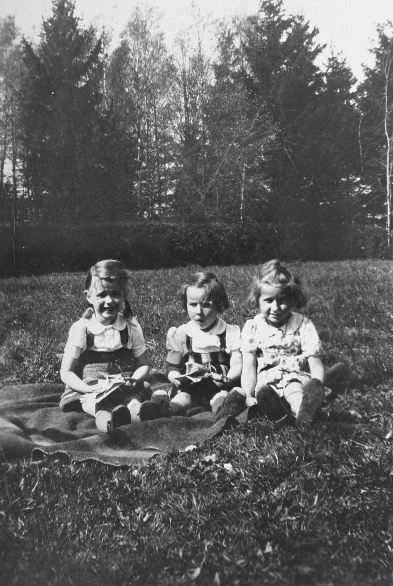 Evelyn (Evy) Goldstein, a Jewish child in hiding, poses with the children of a Nazi officer, whose family was quartered on the estate of Baroness von Huellensen in Bloestan,East Prussia during part of the period Evelyn was there.  From left to right are Ertmuthe, Heidi and Evy.
