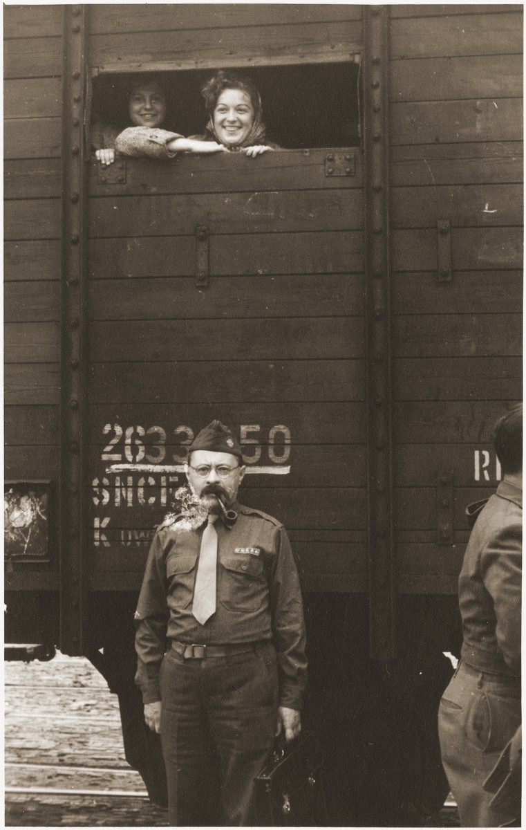 A Jewish social service official poses beneath a train carrying DPs to the port of Bremerhaven, where they will board the Marine Flasher for the U.S.