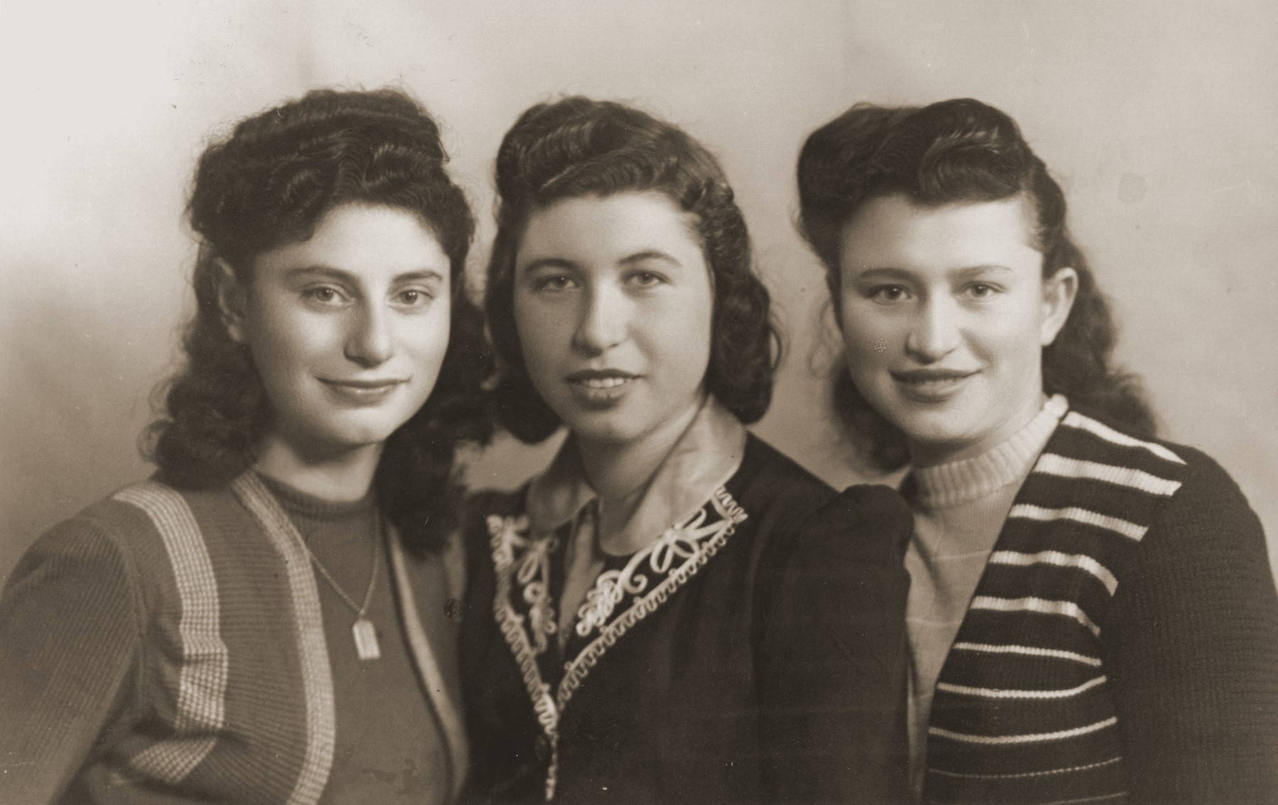 Close-up portrait of three Jewish teenage girls in the Bad Reichenall displaced persons camp.  Rochelle Szklarski is pictured center, with her friends: Shirley Szydlo and Fejga Goldsztajn.