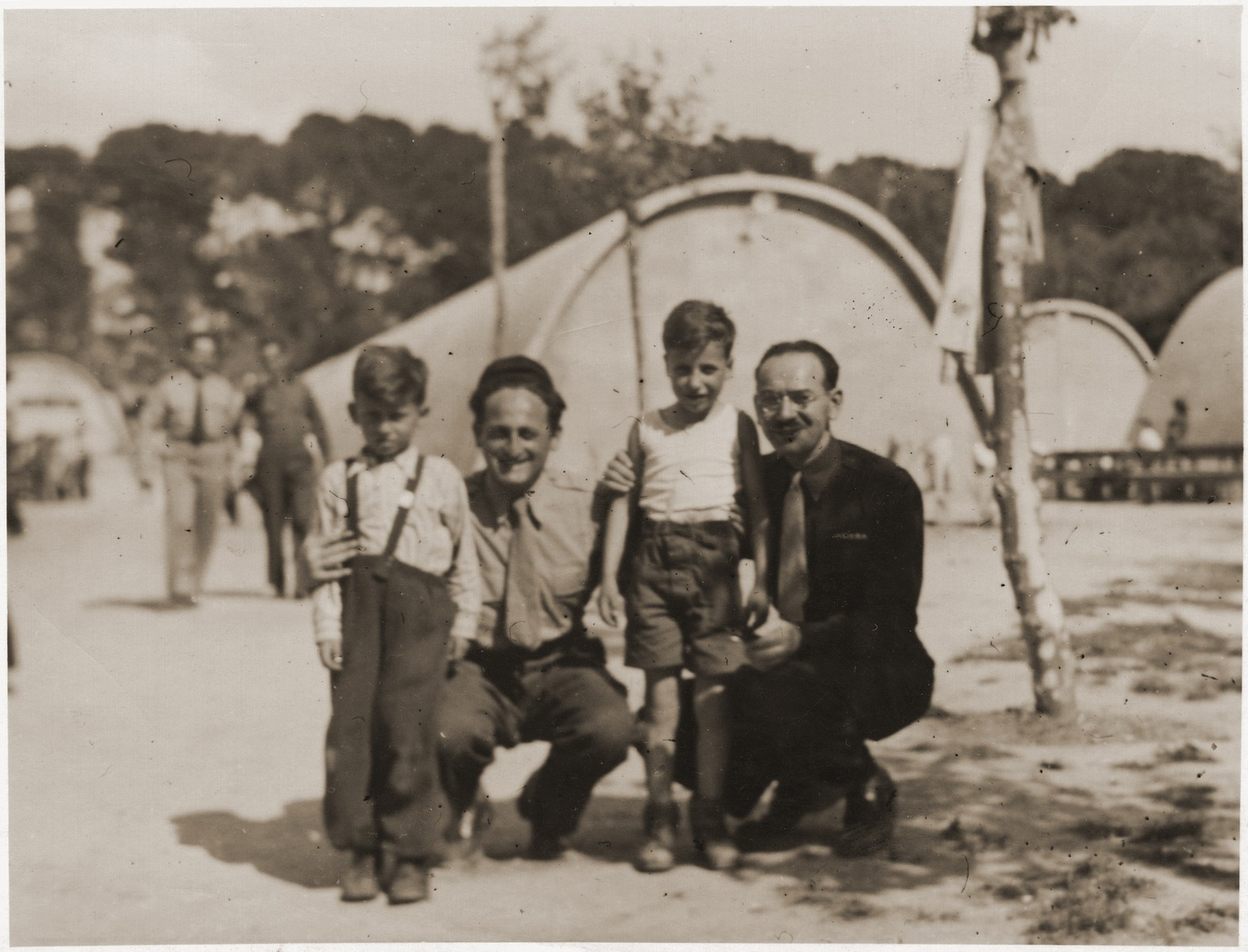 Two Jewish orphans pose with two relief workers at the Marsylia transit camp (a former Yugoslav POW camp) in Marseilles, where they await their departure for Palestine aboard the SS Champollion.    The two boys belong to a group from the Bergen-Belsen displaced persons' camp who have been selected for the first authorized children's transport to Palestine.