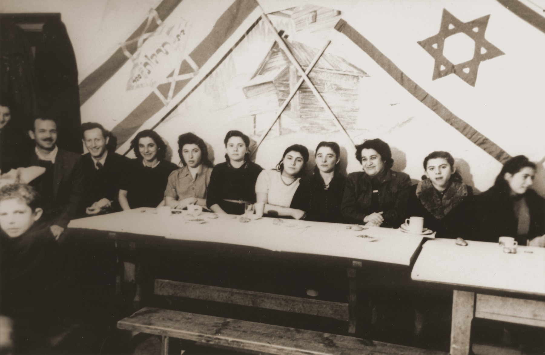 "A group of young people pose in a ""culture hall"" beneath Jewish flags."