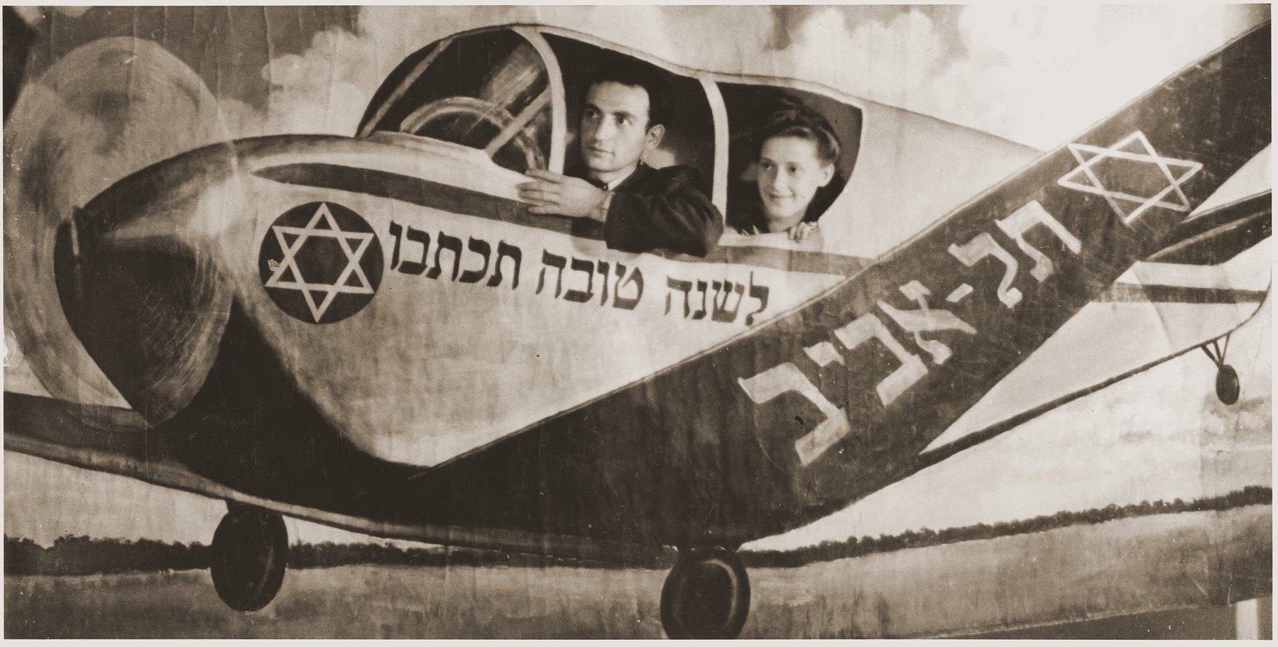 A Jewish New Year's card featuring a young couple from the Fuerth displaced persons camp in an airplane bound for Tel Aviv.