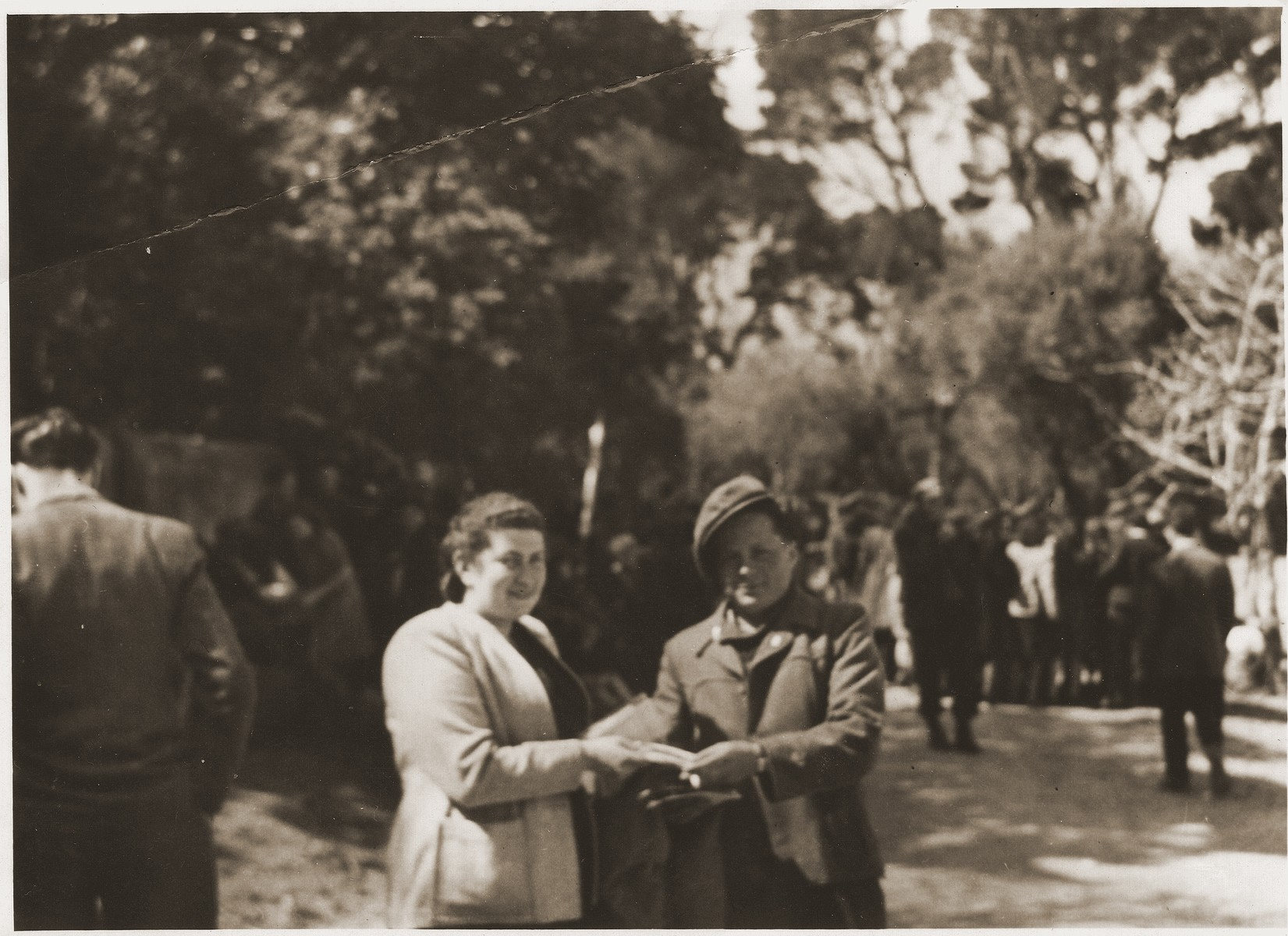 Hadassah Bimko and poses with another DP at the Marsylia transit camp (a former Yugoslav POW camp) in Marseilles.  Bimko icame to Marseilles to accompany a transport of Jewish orphans from the Bergen-Belsen displaced persons' camp who will  board the SS Champollion for Palestine.