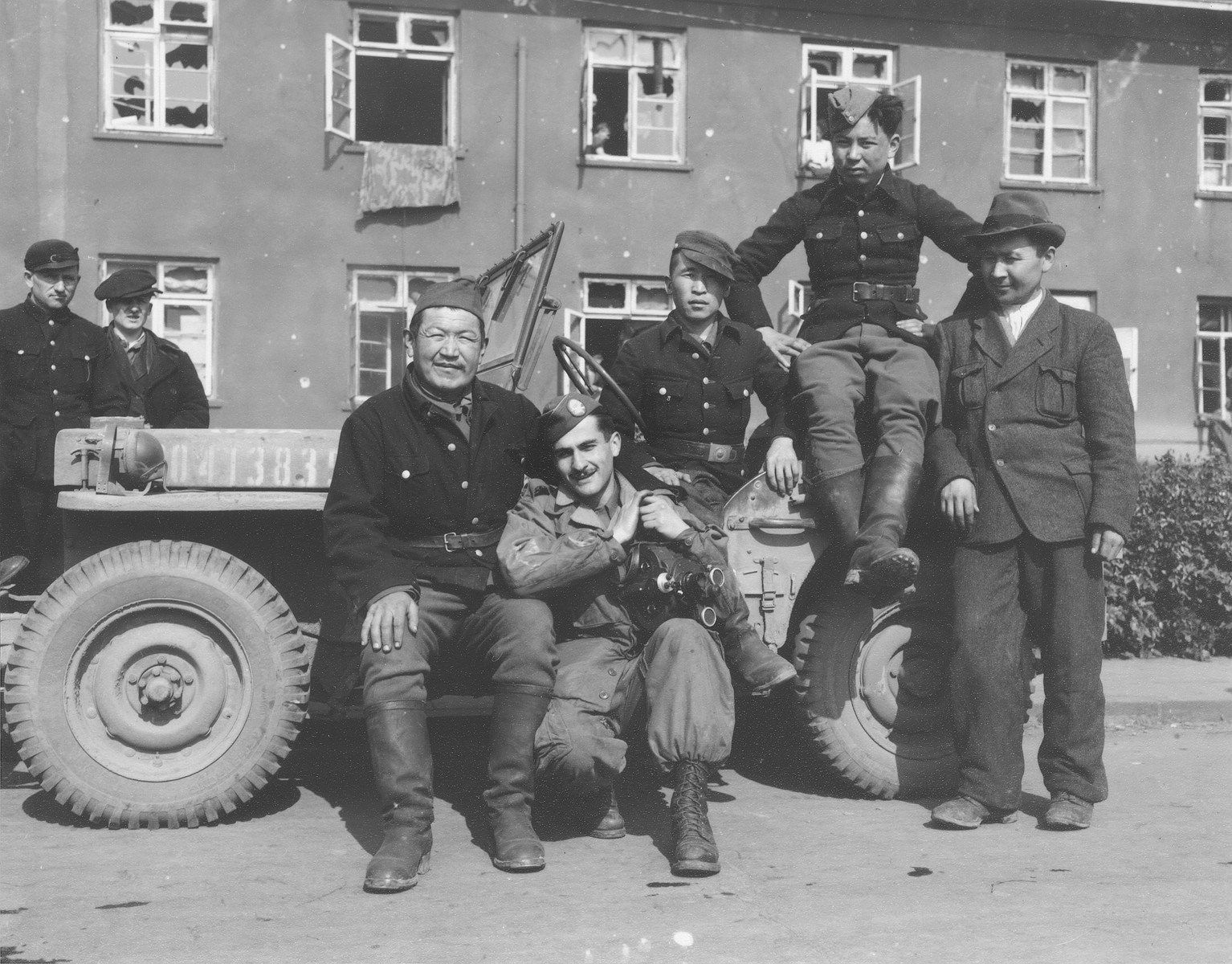 American military photographer Fred Frater poses with Russian soldiers in front of a jeep at their military base in Germany.