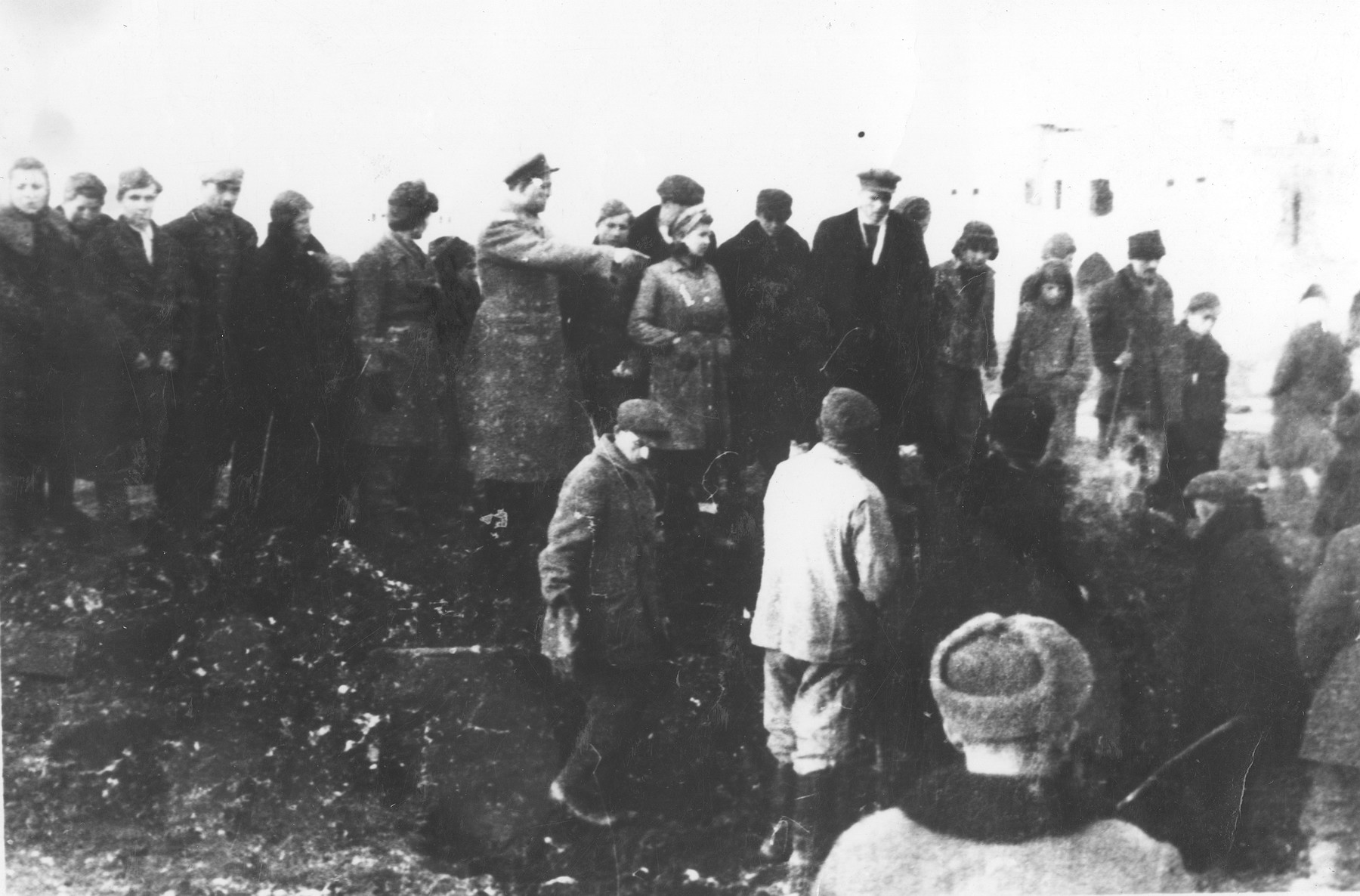 A crowd of people observes the exhumation of a mass grave in the Jewish cemetery of Stanislawow.
