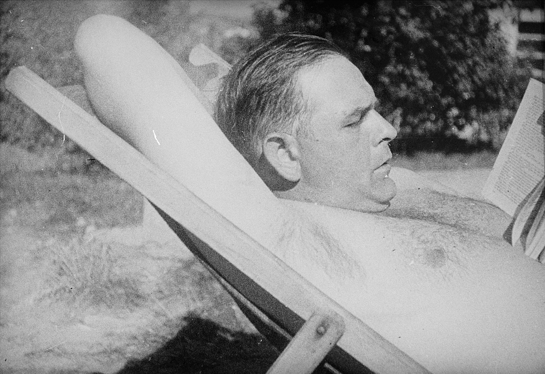 Commandant Amon Goeth reads a book while reclining in a lawn chair at his villa in the Plaszow concentration.