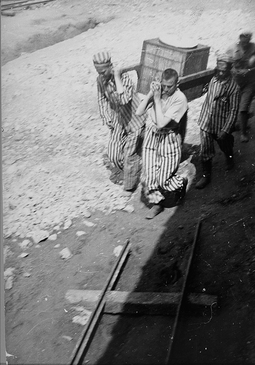 Prisoners in Plaszow transport a food container to others at forced labor.