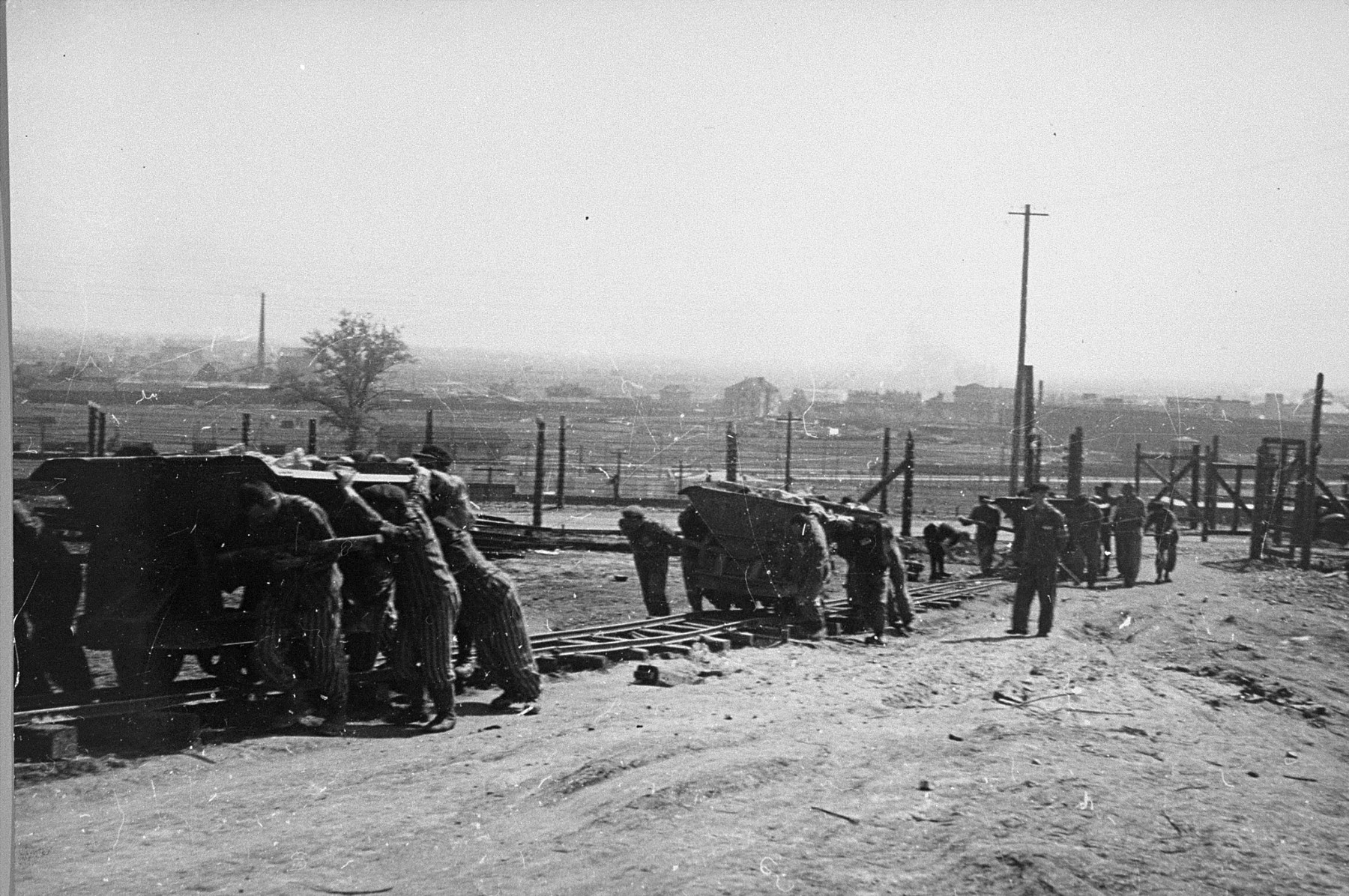 Jewish prisoners in Plaszow at forced labor.  The man at right is a Kapo.