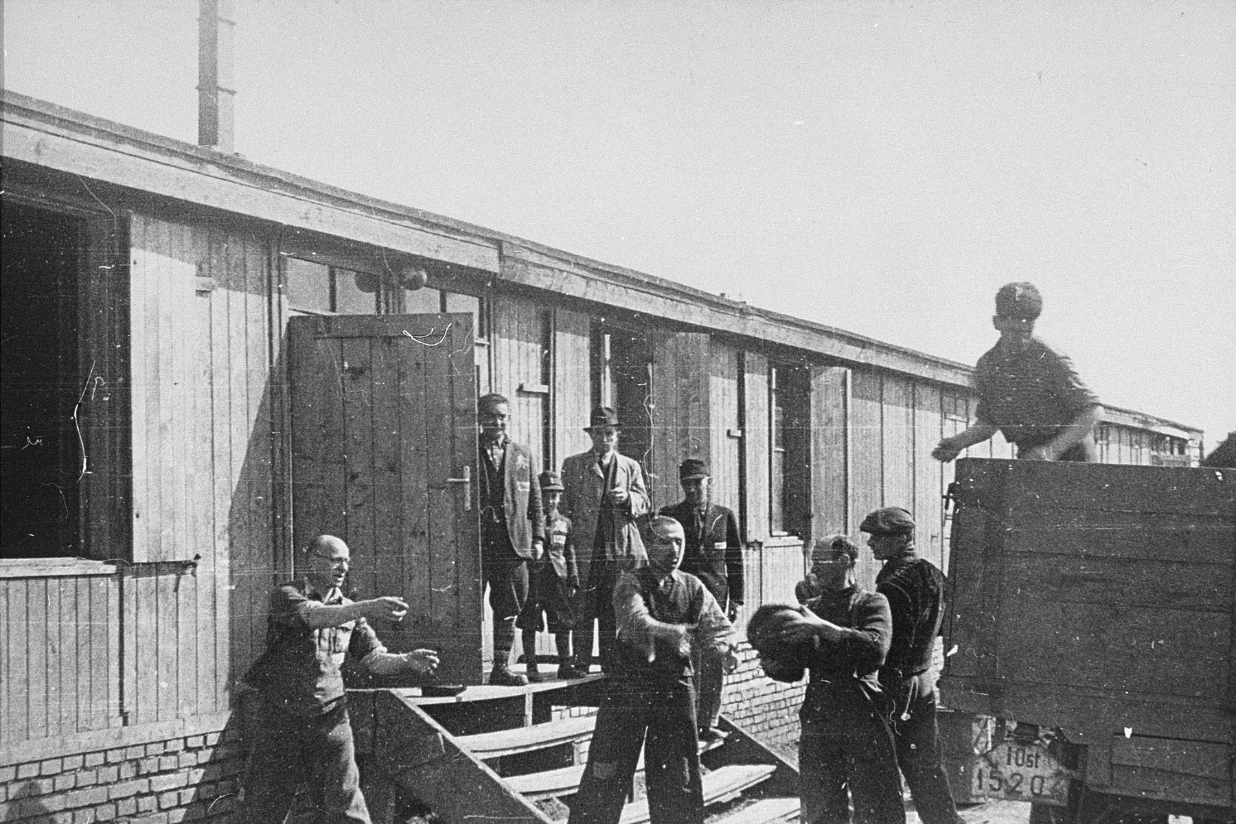 Jewish prisoners in Plaszow unload bread into part of the Madritch factory.    The Madritch factory utilized concentration camp labor to produce uniforms for the German army.