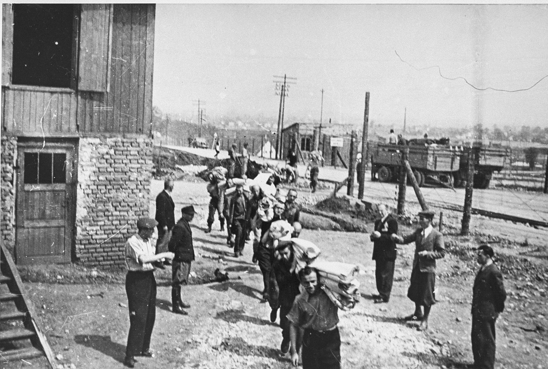 Jewish prisoners carry bolts of cloth to the Madritch factory in Plaszow.  The Madritch factory utilized concentration camp labor to produce uniforms for the German army.