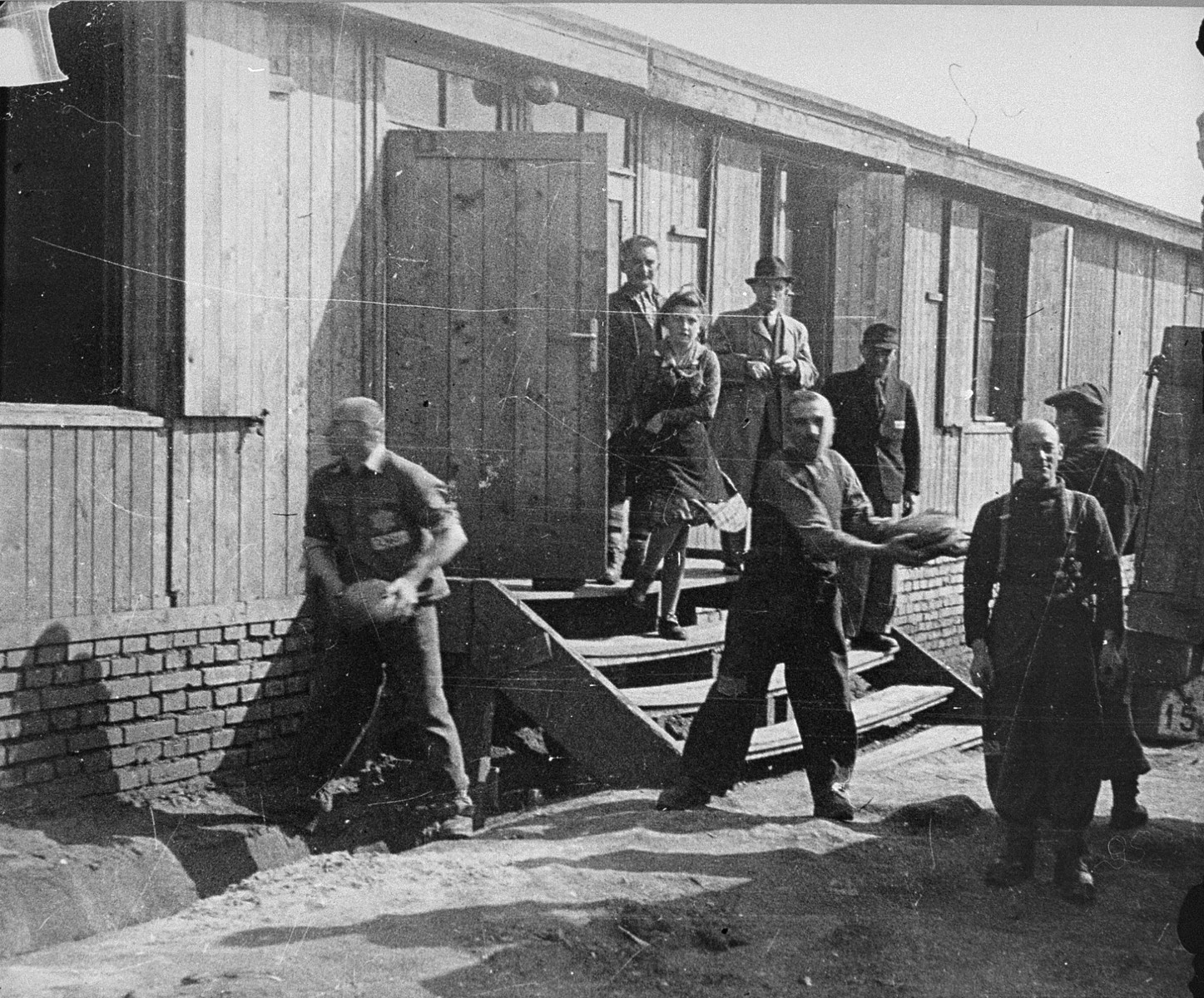 Jewish prisoners in Plaszow unload bread into the Madritch factory.  The Madritch factory utilized concentration camp labor to produce uniforms for the German army.  Pictured on the steps are Samuel Brand and his wife, Ala Fass Brand.