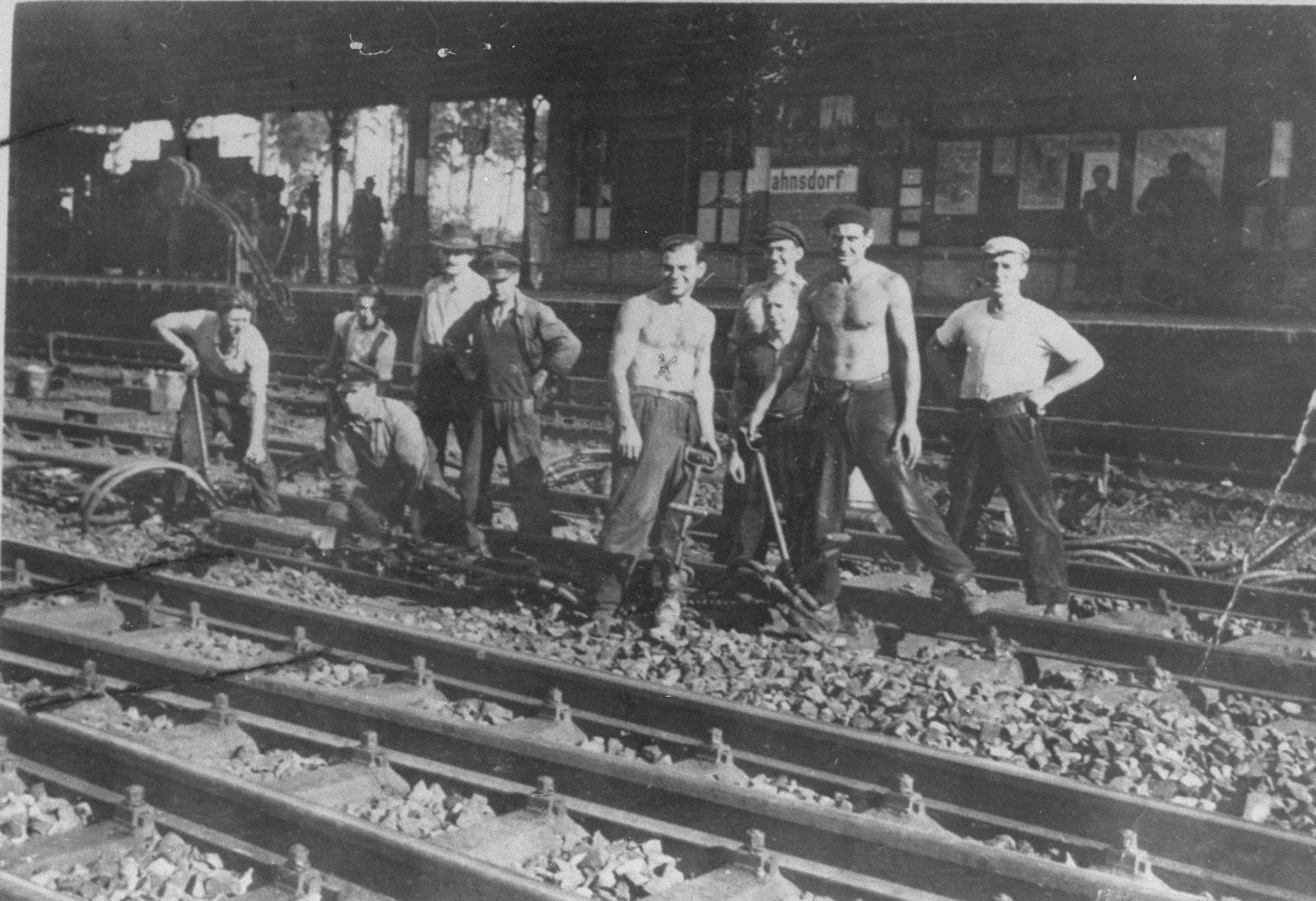 A group of Jewish prisoners from Oranienburg (Trup 8 Coepenick) at forced labor repairing railroad tracks in front of the Rahnsdorf train station.    The donor, Lutz Haase, is pictured in the center, chained to his jack hammer.  The Nazi foreman of the labor brigade is pictured next to Haase with his hands on his hips.  At the far left is a Jewish prisoner  who was about to be given temporary leave from the camp to visit his wife and newborn in a hospital in Berlin, when a camp guard, who was stationed at  the entrance gate to Oranienburg, intentionally re-activated the electrified fence as he was leaving.  When the prisoner touched the gate he was electrocuted.