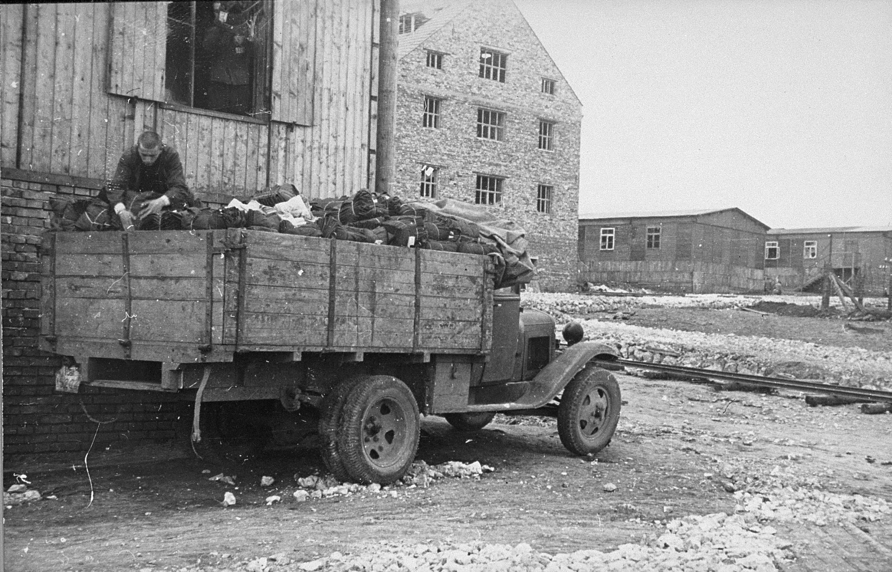 Jewish prisoners load textiles onto a truck from a Madritch factory warehouse.  The Madritch factory utilized concentration camp labor in Plaszow to produce uniforms for the German army.