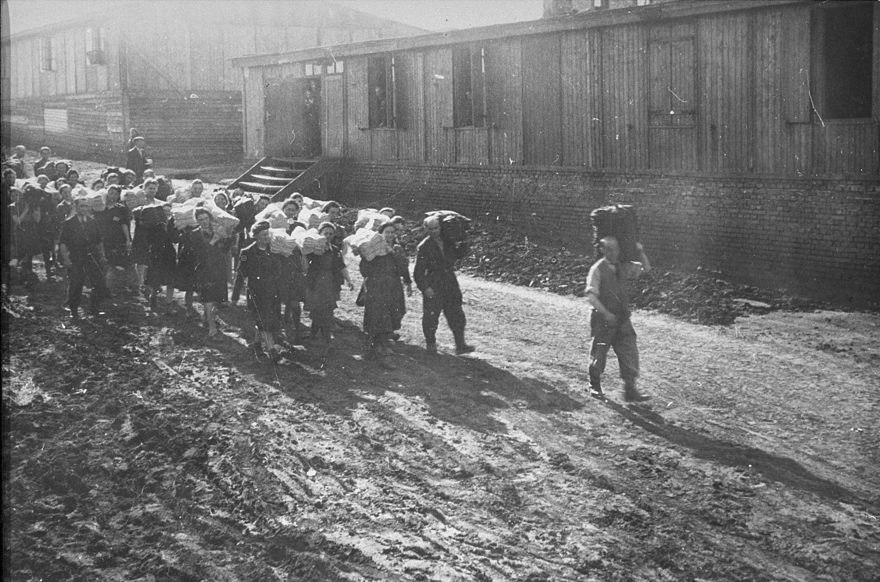 Jewish prisoners carry cloth to the Madritch factory.  The Madritch factory utilized concentration camp labor to produce uniforms for the German army.