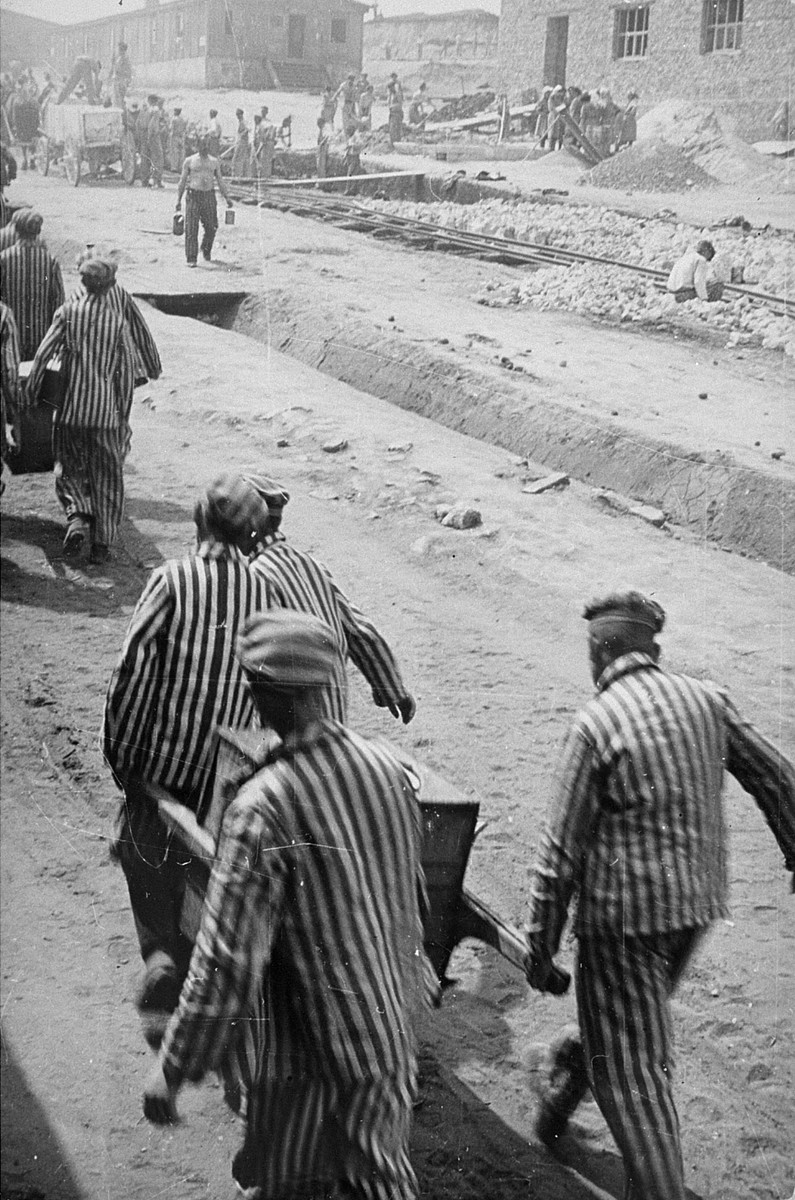 Prisoners in Plaszow carry food containers to a work site where it will be distributed.