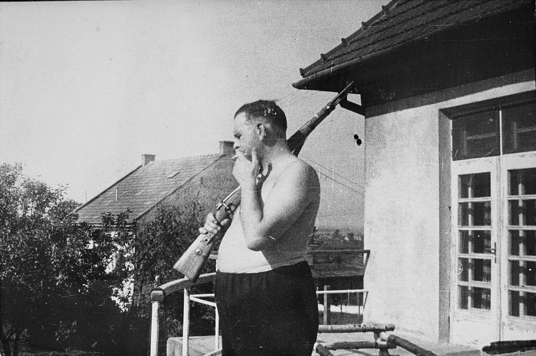 Commandant Amon Goeth stands with his rifle on the balcony of his villa in the Plaszow concentration camp.