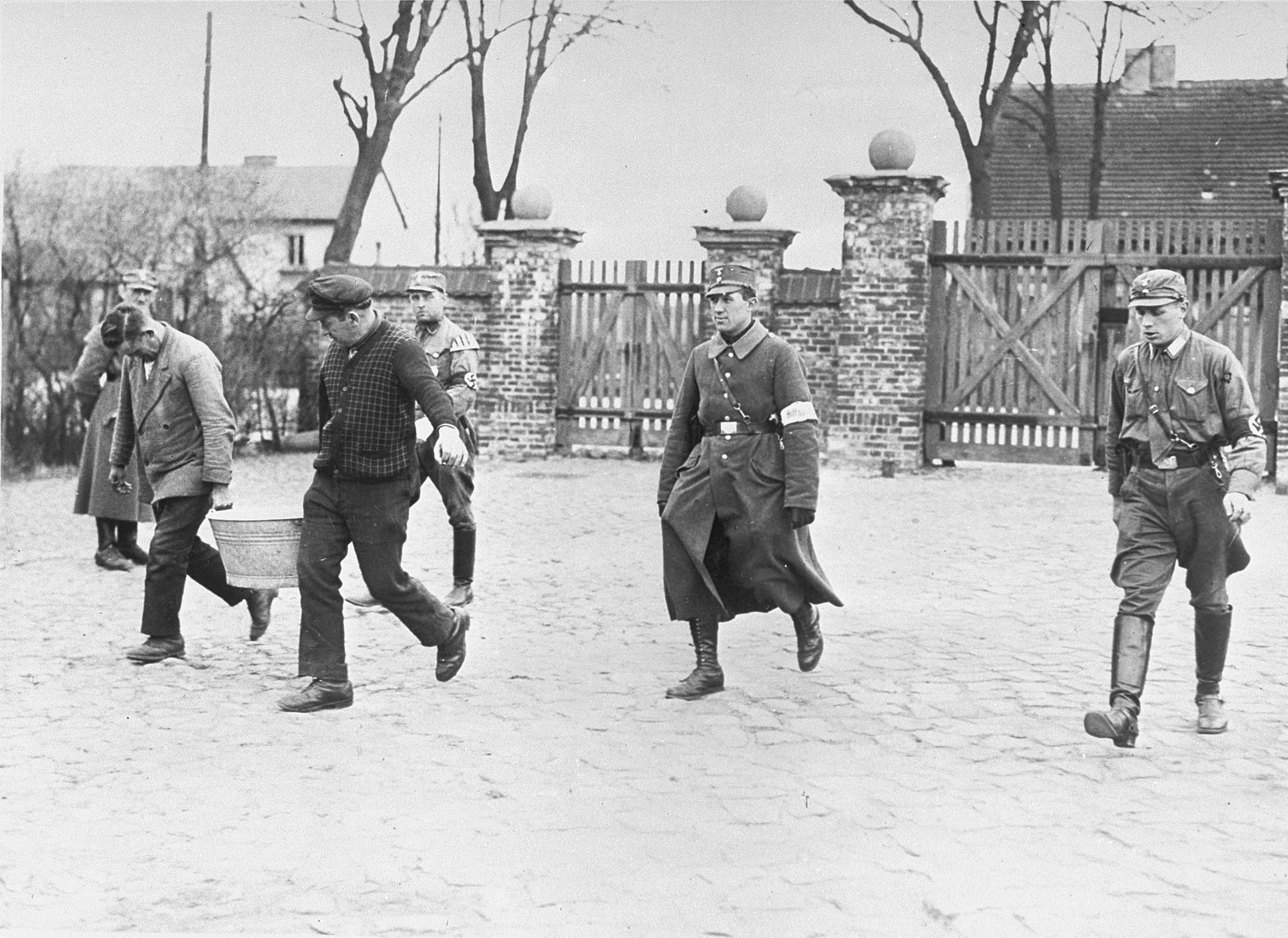 SA guards oversee prisoners who are carrying a tub near the entrance to the Oranienburg concentration camp.
