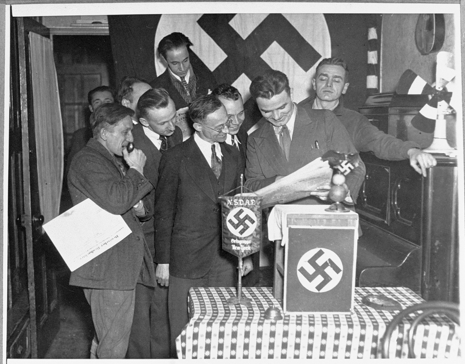 Paul Manger reads a newspaper article announcing Hitler's appointment as German Chancellor to fellow  members of the Nazi party at a celebration in New York.
