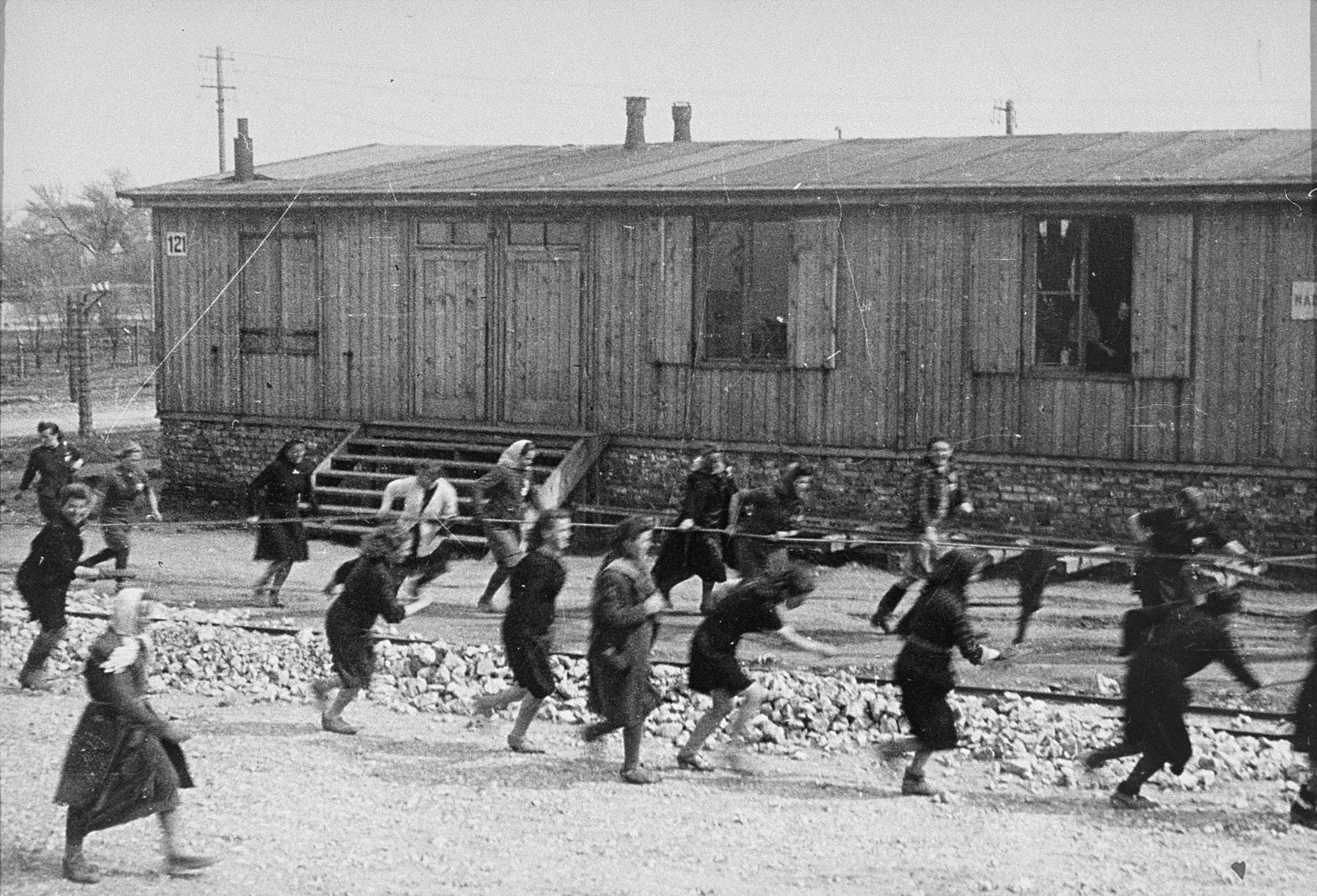 "Jewish women at forced labor in Plaszow.  Behind them is barrack #121, which was owned by the clothing firm of J. Madritch of Vienna.  Its workshops on ""Industry Street"" in the camp were an independent organization within the DAW (German Arms Institution)."