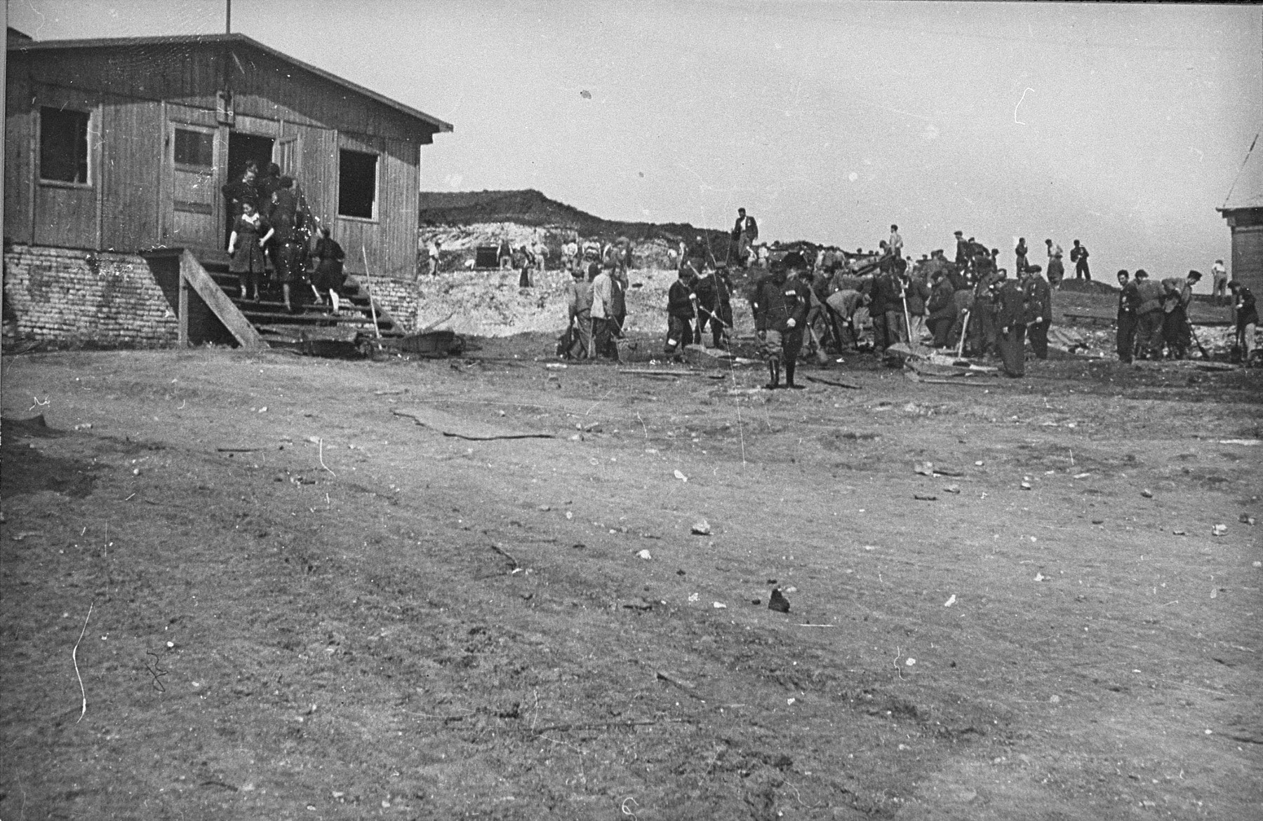 Jewish prisoners at forced labor in Plaszow.  The building on the left is probably the Madritch factory office, while the man walking in the foreground is likely a kapo, or civilian overseer.