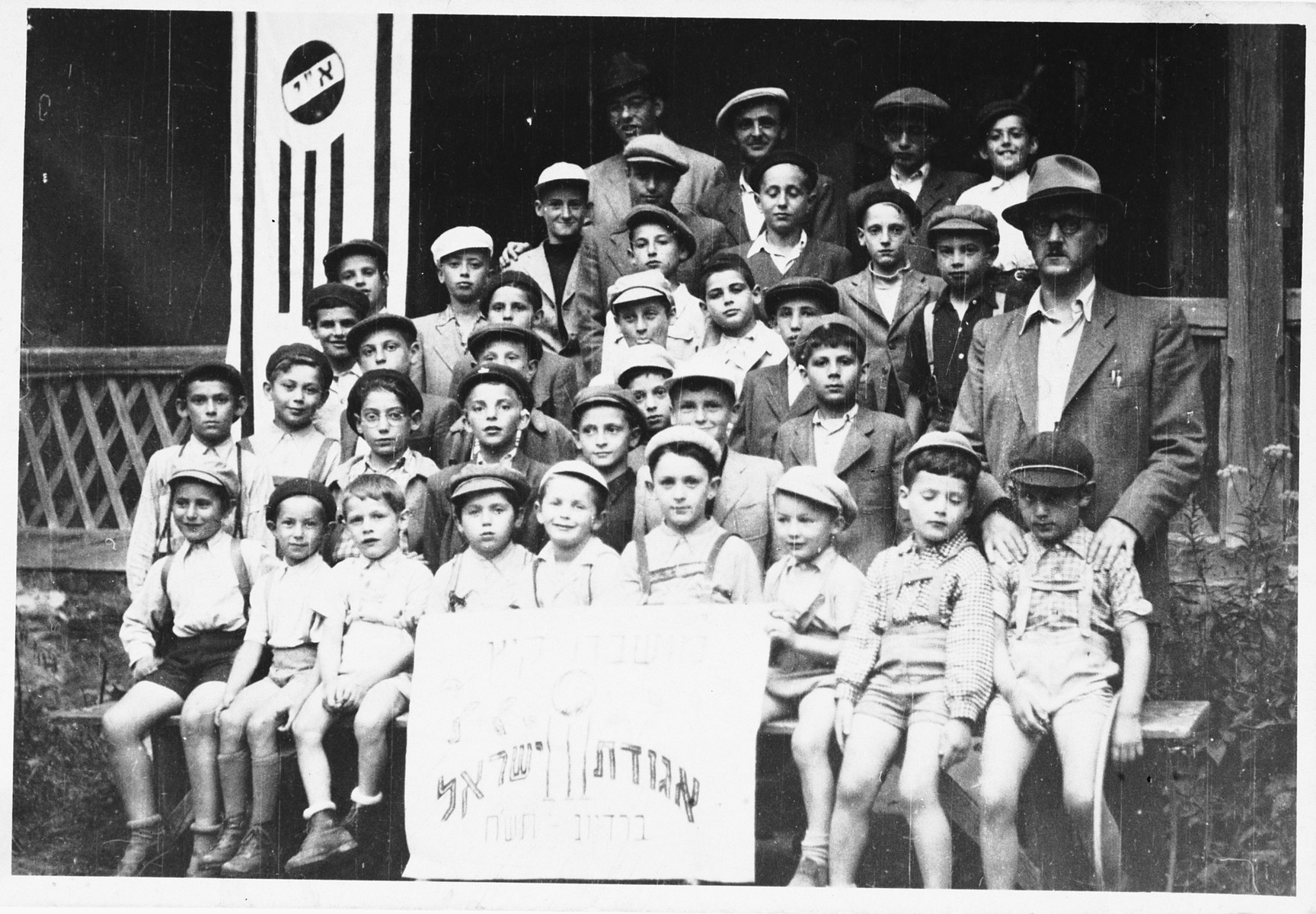 A group of orphans an Agudat Yisrael children's home in Bratislava  Among those pictured is Akiva Yosef Weiss, the teacher. Yehuda (Ernest) Schlessinger  first on the left, sixth row from the bottom. Itschak (Tibor) Schlessinger is sixth from the left, second row from the bottom. Both boys are nephews of the teacher.    Moshe Tomas is seated in the first row, fifth from the left.