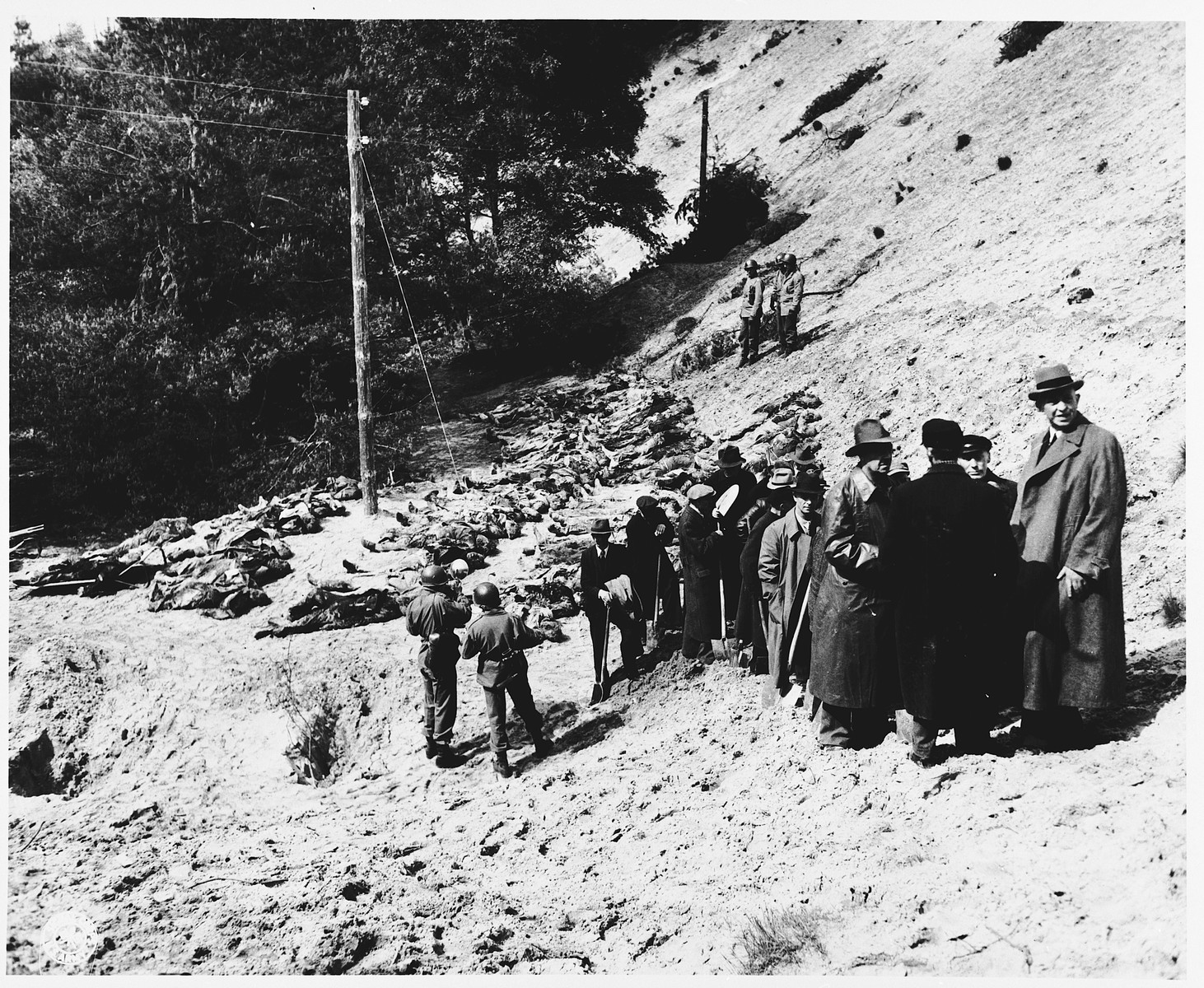 Under the supervision of American soldiers, German civilians view the bodies of 71 political prisoners from a mass grave on Wenzelnberg near Solingen-Ohligs.    The victims, most of whom were taken from Luettringhausen prison, were shot and buried by the Gestapo following orders to eliminate all Reich enemies just before the end of the war.
