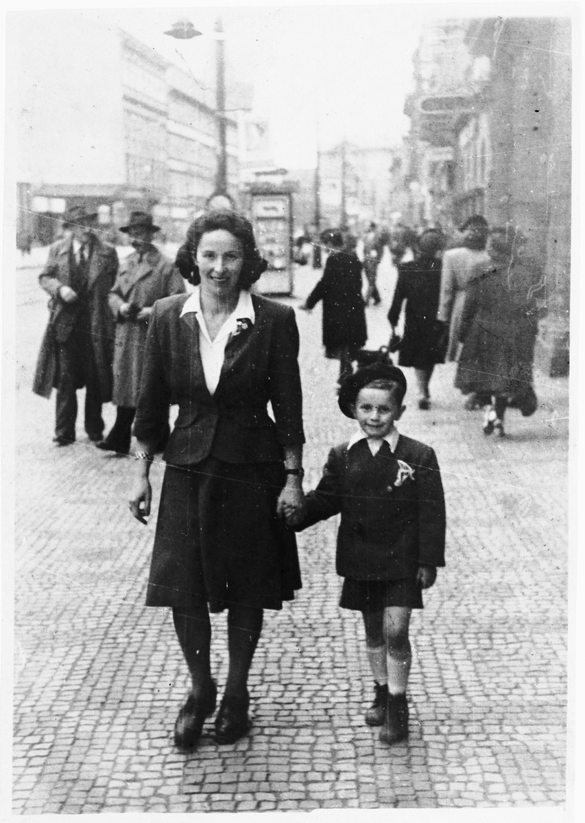 A Jewish woman walks down the street, hand in hand with her young son.  Pictured are Berte Akerman and Moshe Tomas.