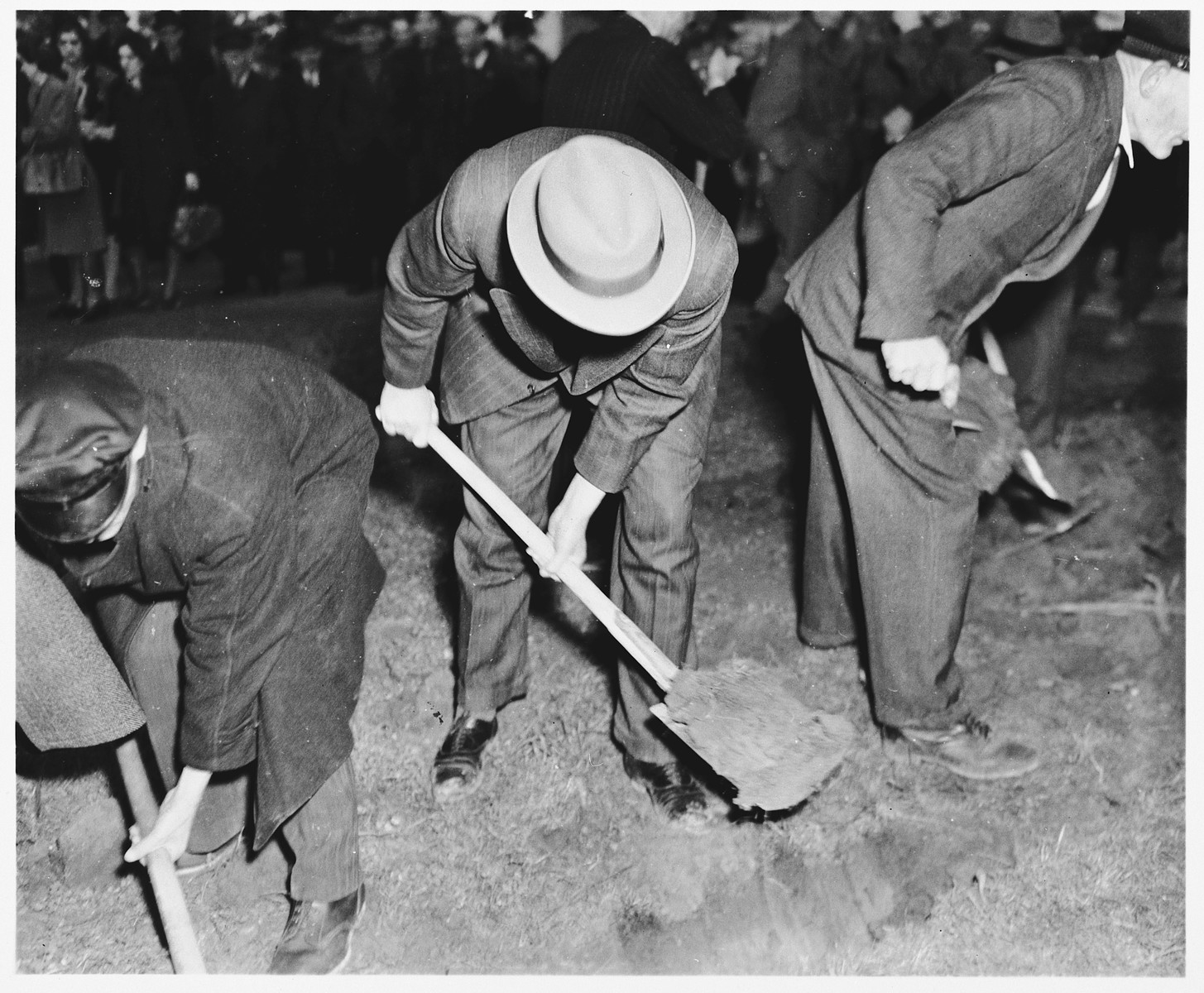 German civilians dig graves for the bodies of 71 political prisoners, exhumed from a mass grave on Wenzelnberg near Solingen-Ohligs, in front of the city hall.    The victims, most of whom were taken from Luettringhausen prison, were shot and buried by the Gestapo following orders to eliminate all Reich enemies just before the end of the war.