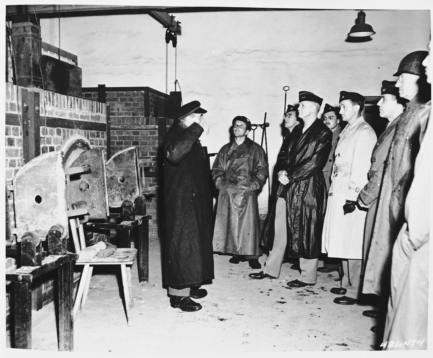 A former prisoner explains the working of the crematoria in Dachau to a delegation of American officers.  Among those pictured is Major General William R. Arnold (fourth from right), Chief of Chaplains Corps, 7th U.S. Army.