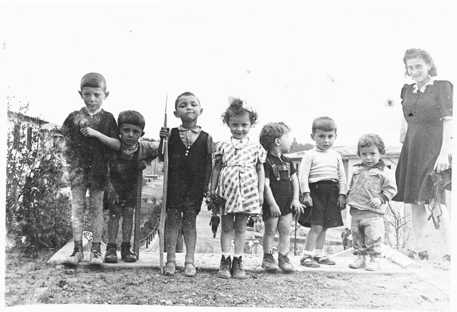 A group of Jewish preschoolers pose outside with their teacher at the Schlachtensee displaced persons camp.