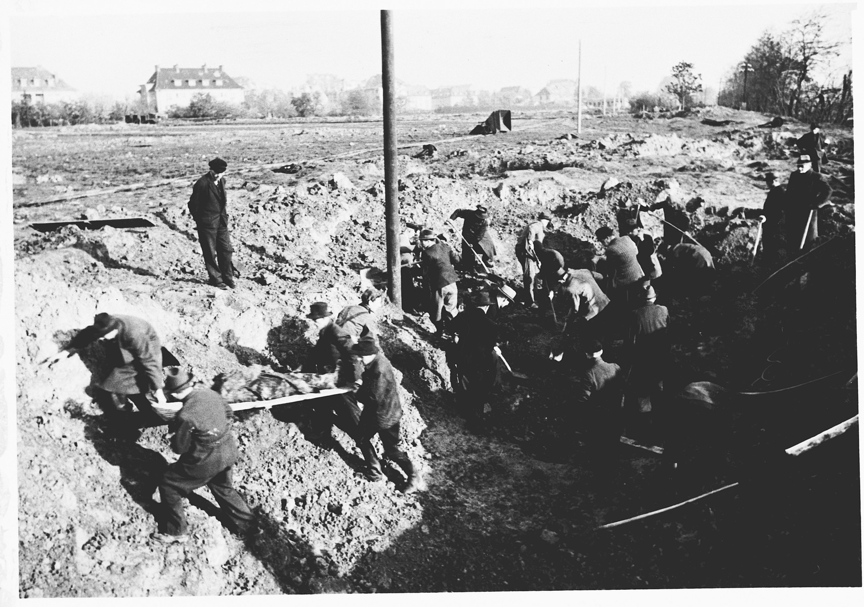 German civilians exhume the corpses of Italians shot in shell holes on the orders of the Gestapo in Wilhelmshoehe on March 31, 1945.
