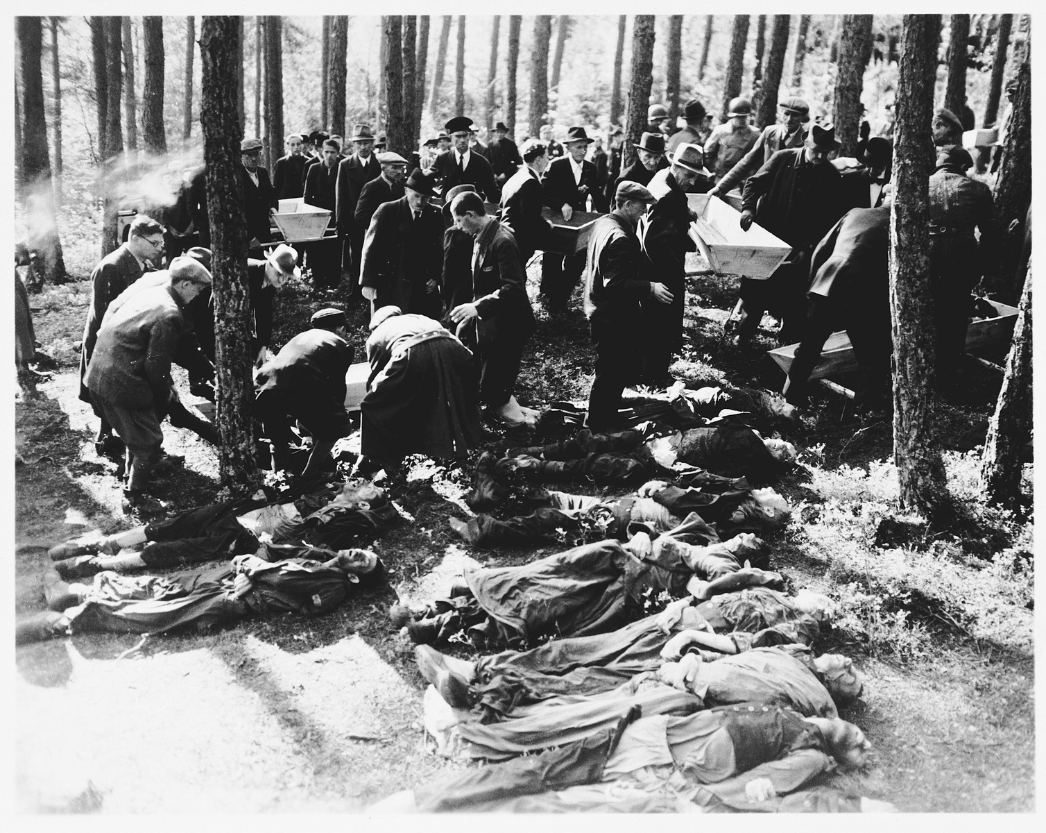 "Under the supervision of American soldiers, German civilians from Neunburg vorm Wald place corpses into coffins for transportation to the town cemetery where they will be properly buried.    The victims were Polish, Hungarian, and Russian Jews shot near Neunburg while on a death march from Flossenbuerg.  The original caption reads, ""Putting the bodies of the slave laborers in coffin made by civilians in preparation for the mile and a half treak to the burial grounds outside Nurnburg, Germany."" [sic]"