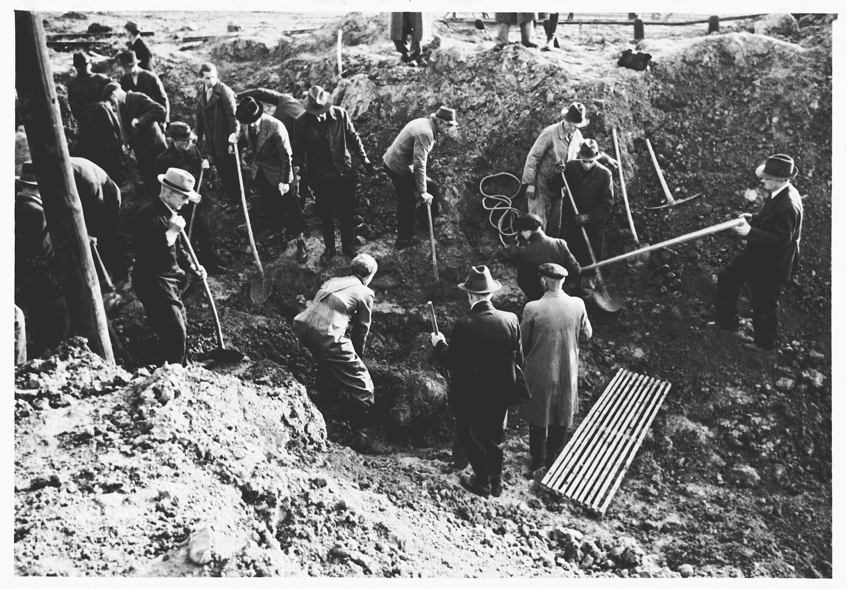 German civilians exhume the corpses of Italians shot and buried in shell holes on the orders of the Gestapo in Wilhelmshoehe on March 31, 1945.